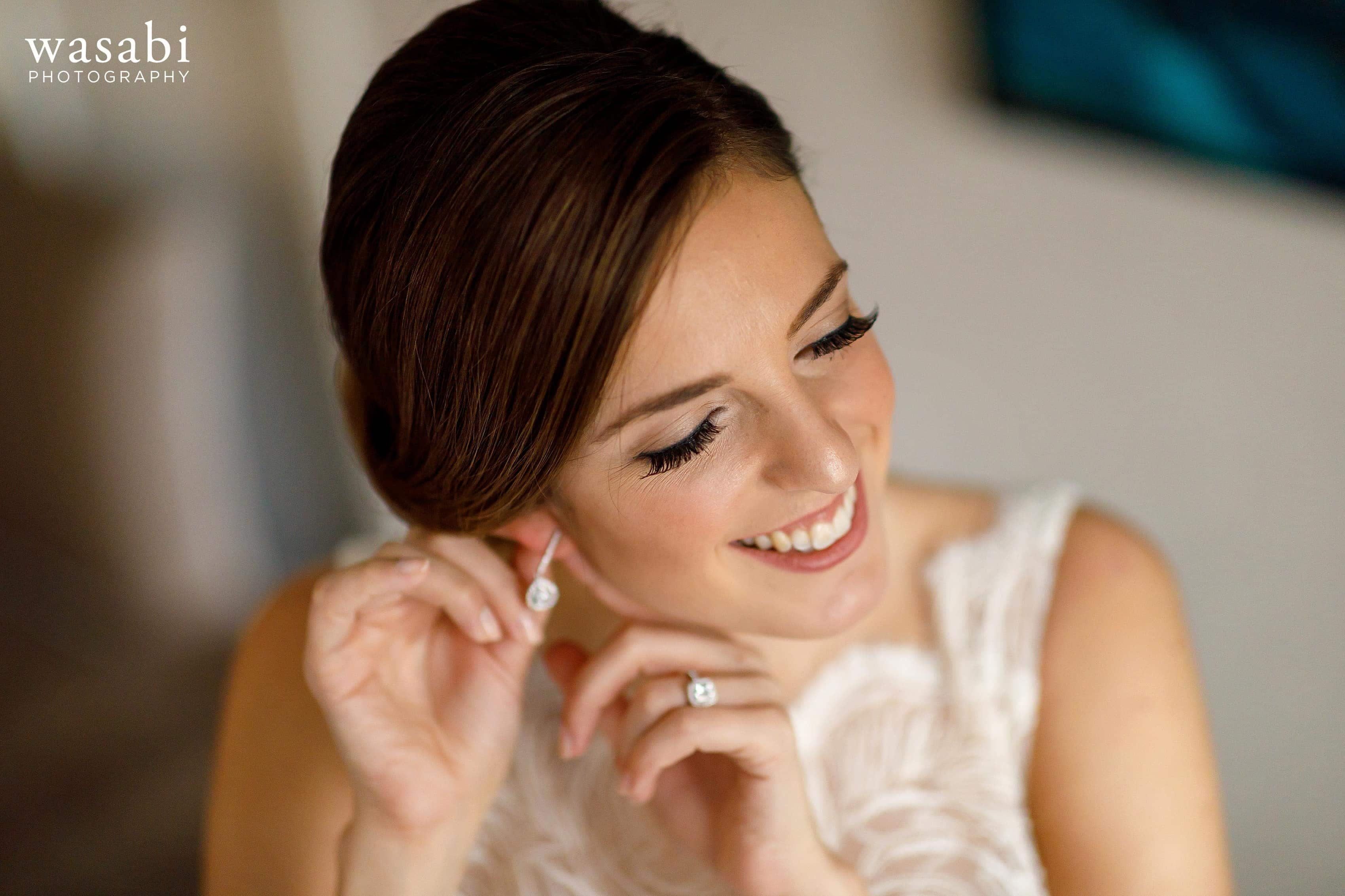 bride puts on earrings in the presidential suite while getting ready for wedding at InterContinental Chicago Magnificent Mile Hotel