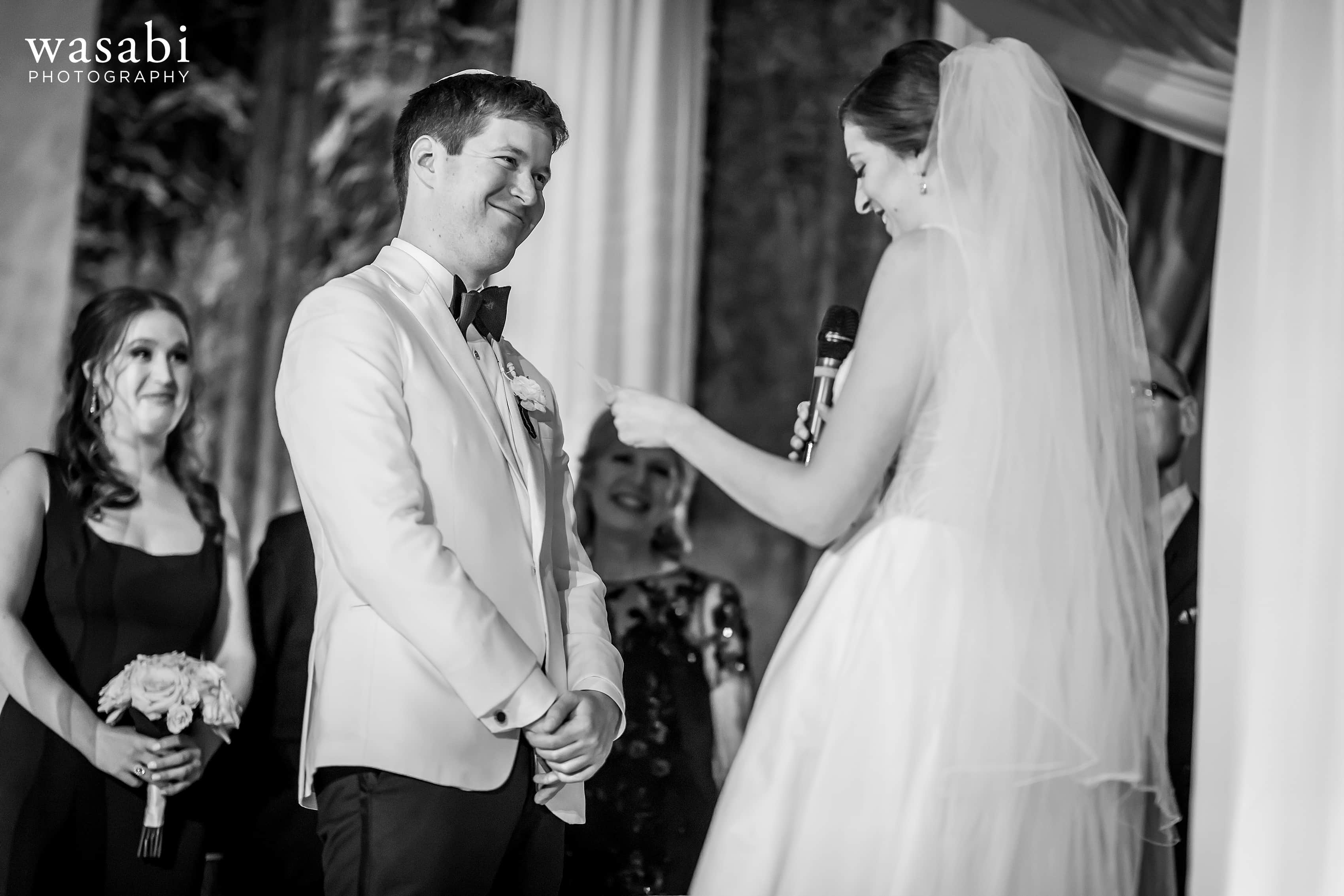 bride smiles at bride during vows in Jewish wedding ceremony at InterContinental Chicago Magnificent Mile Hotel