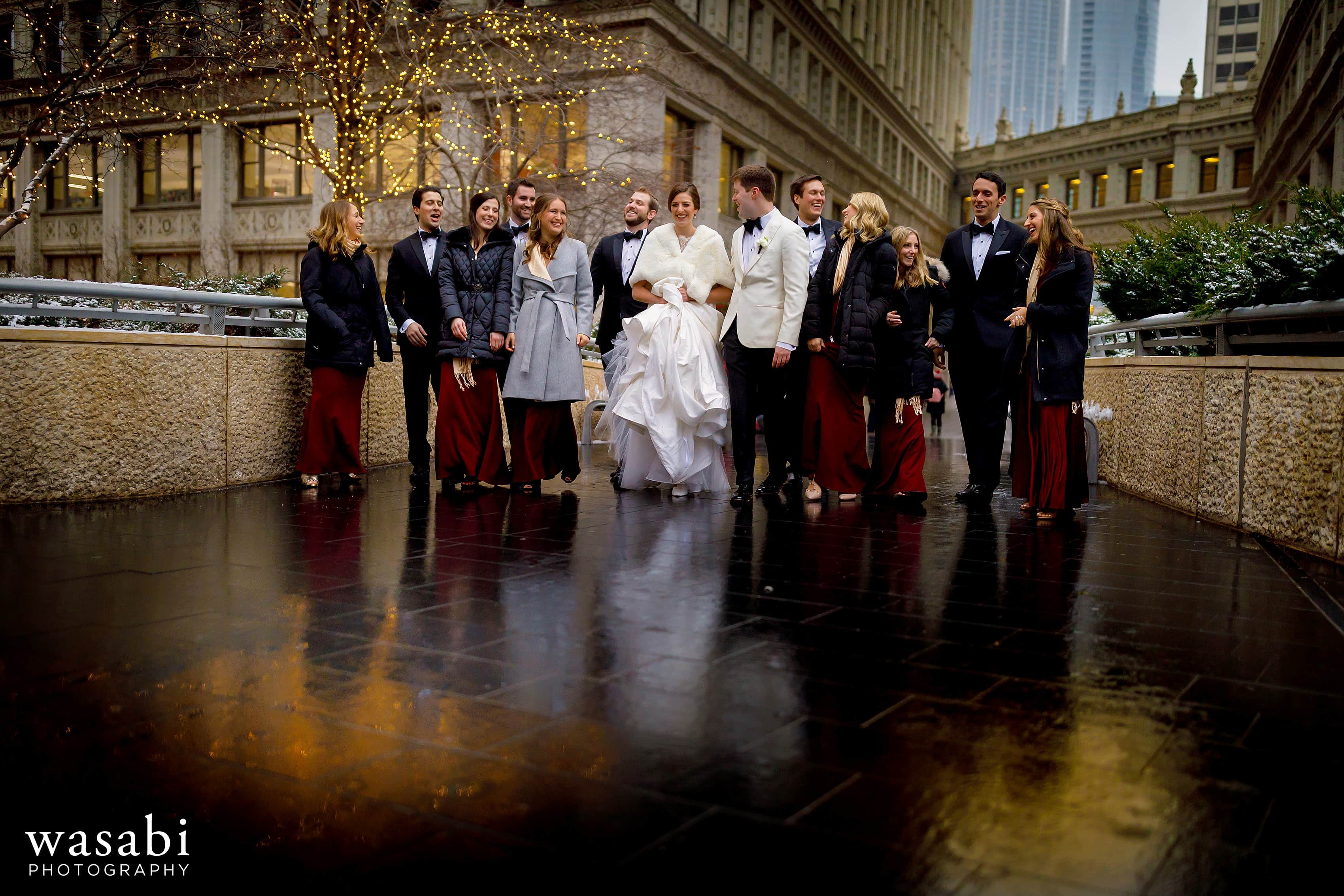 wedding party walks under the Wrigley Building in downtown Chicago during winter wedding