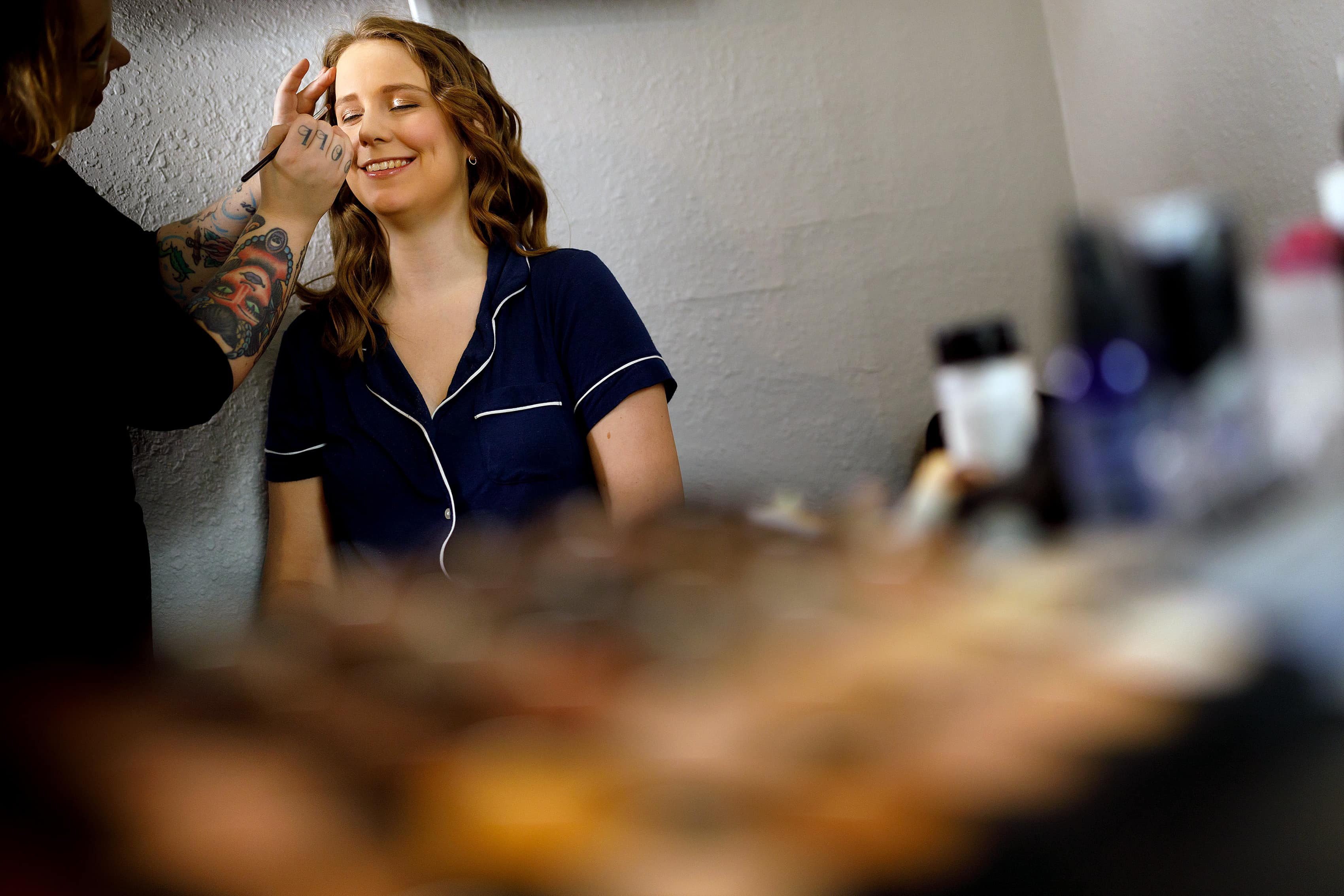 bride has her makeup done while getting ready for wedding