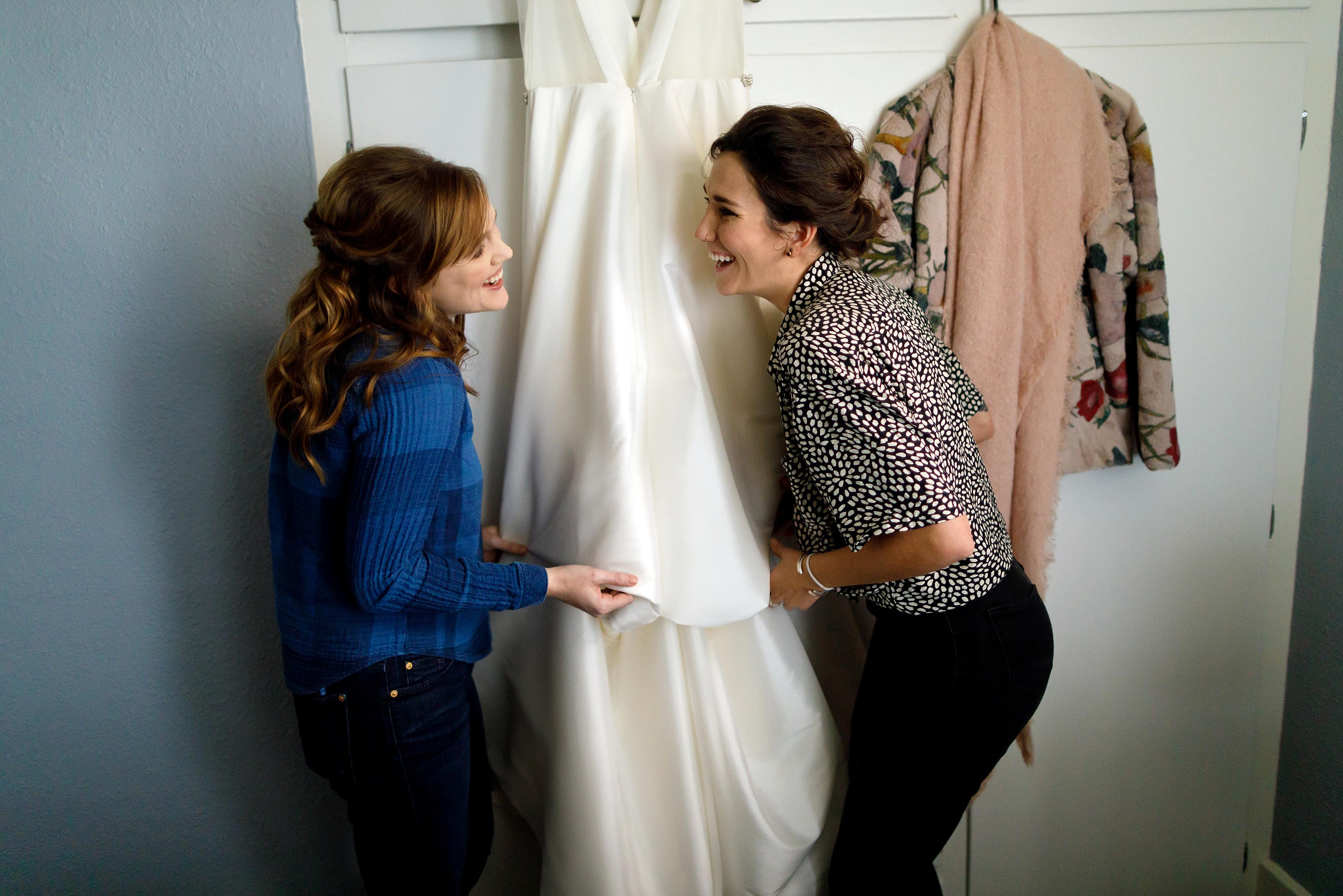 bridesmaids laugh in front of wedding dress
