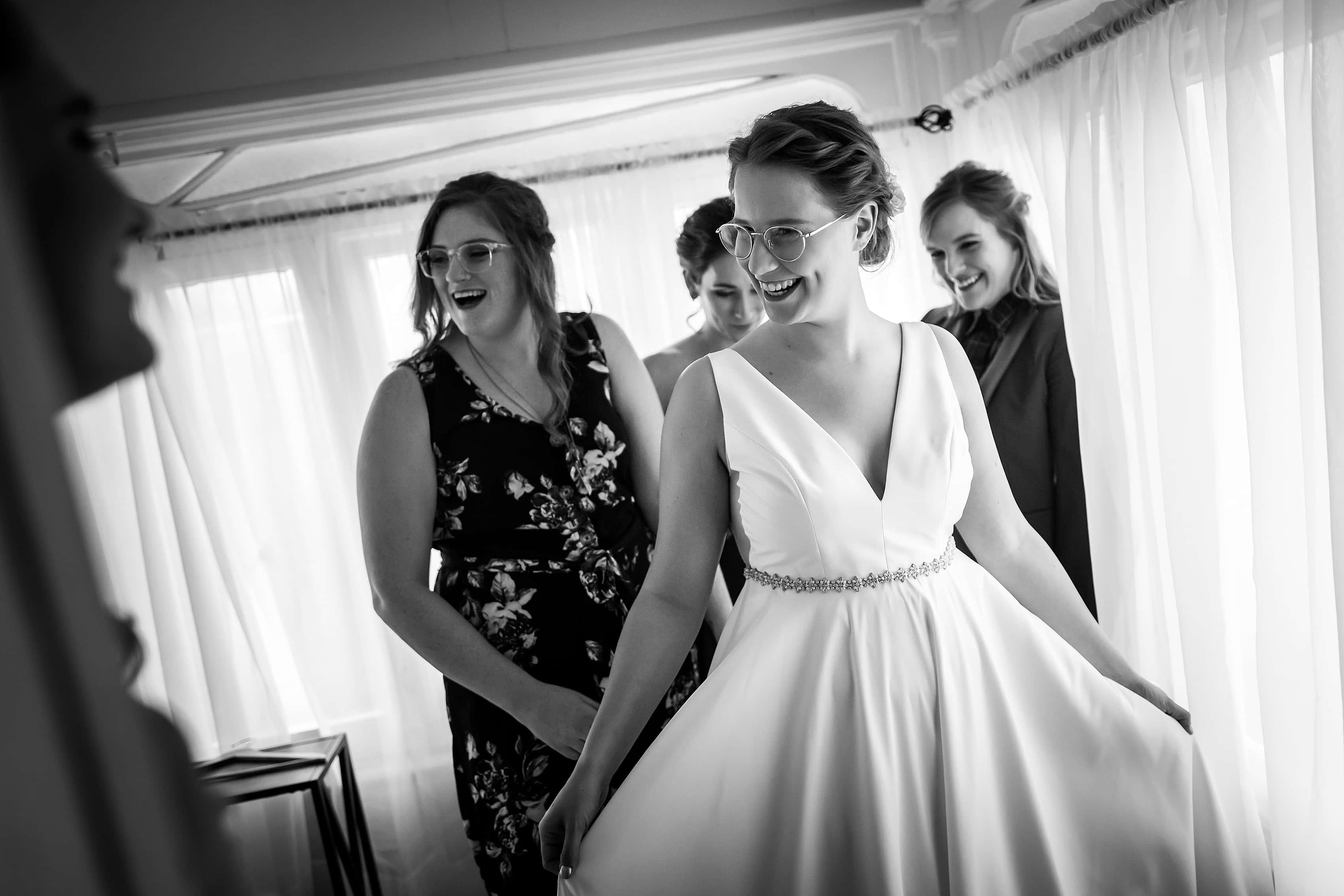 bridesmaids help bride into wedding dress
