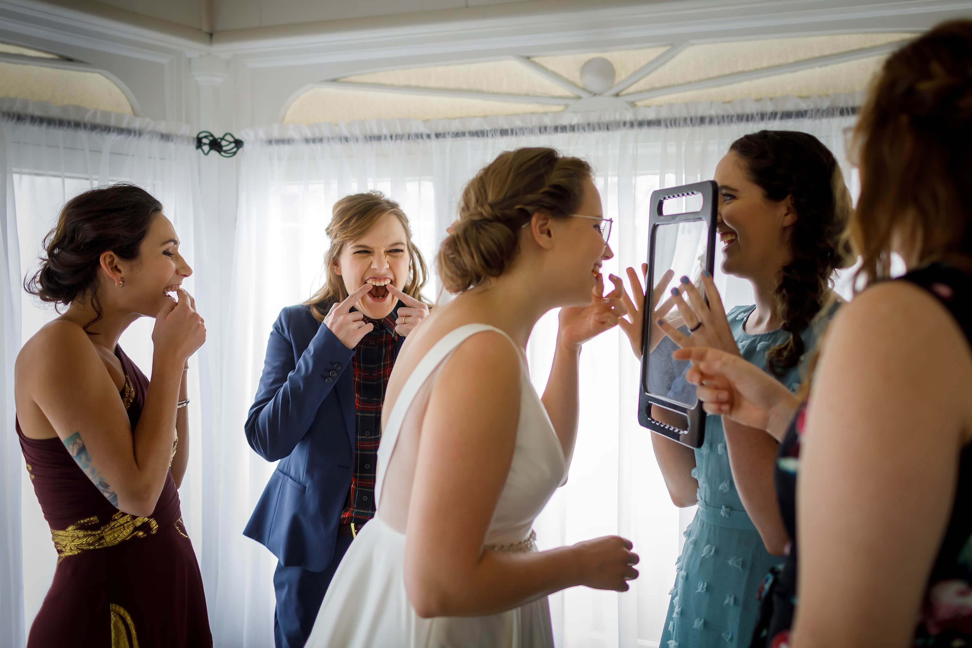 bridemaids help bride get the lipstick off her teeth while getting ready for wedding