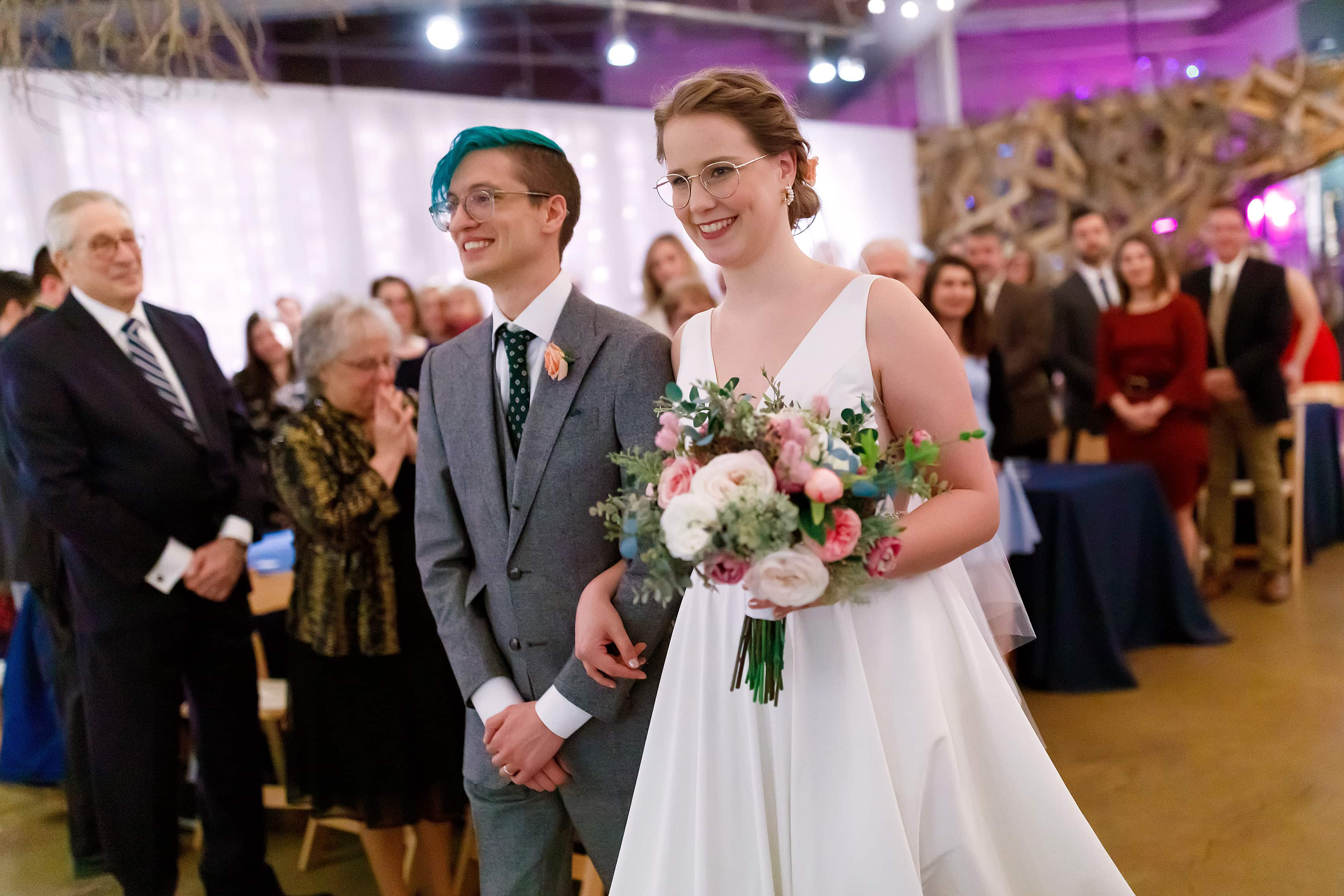 bride and groom walk down aisle during wedding ceremony at Rust Belt Market in downtown Ferndale, Michigan