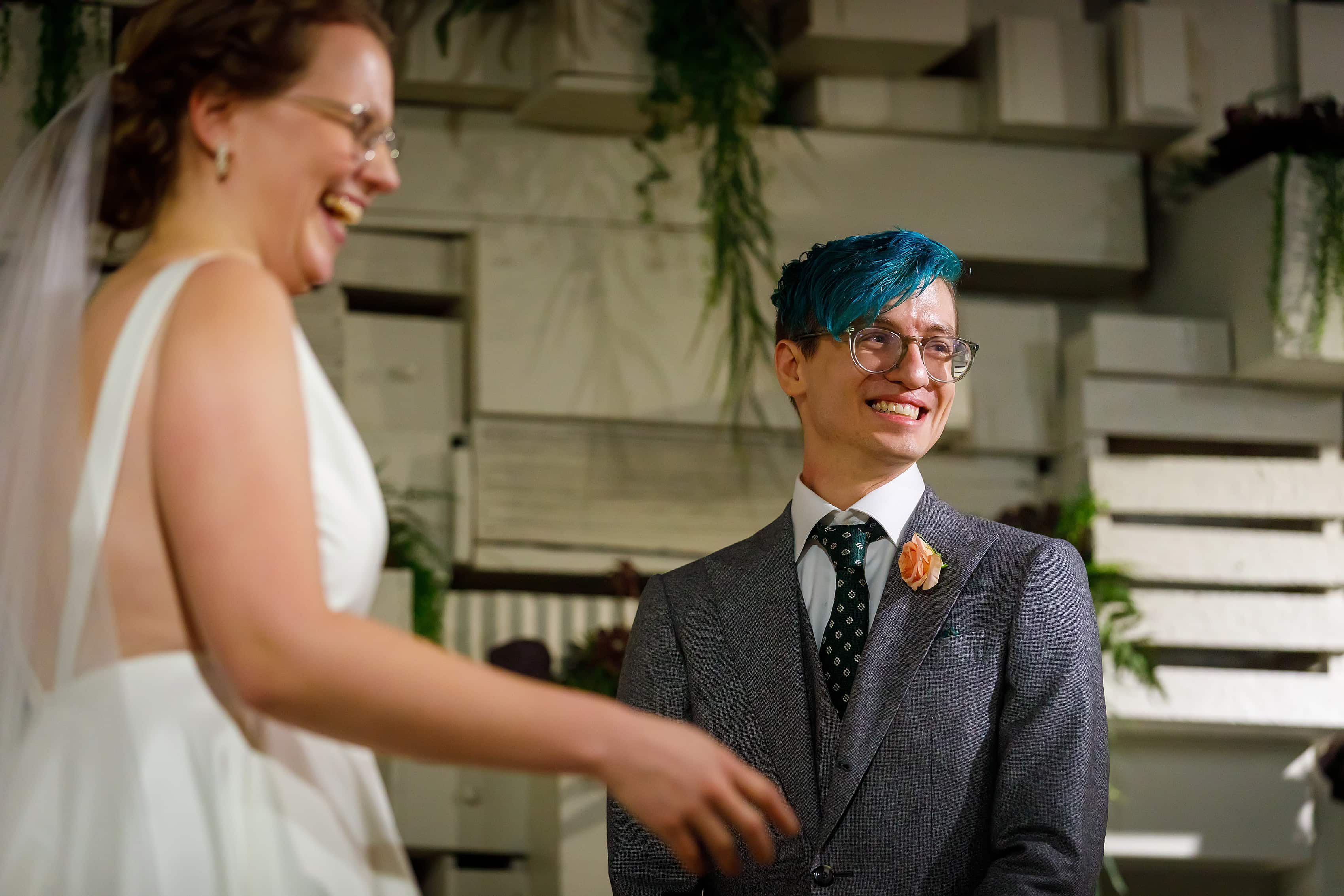 bride and groom laugh during wedding ceremony at Rust Belt Market in downtown Ferndale, Michigan
