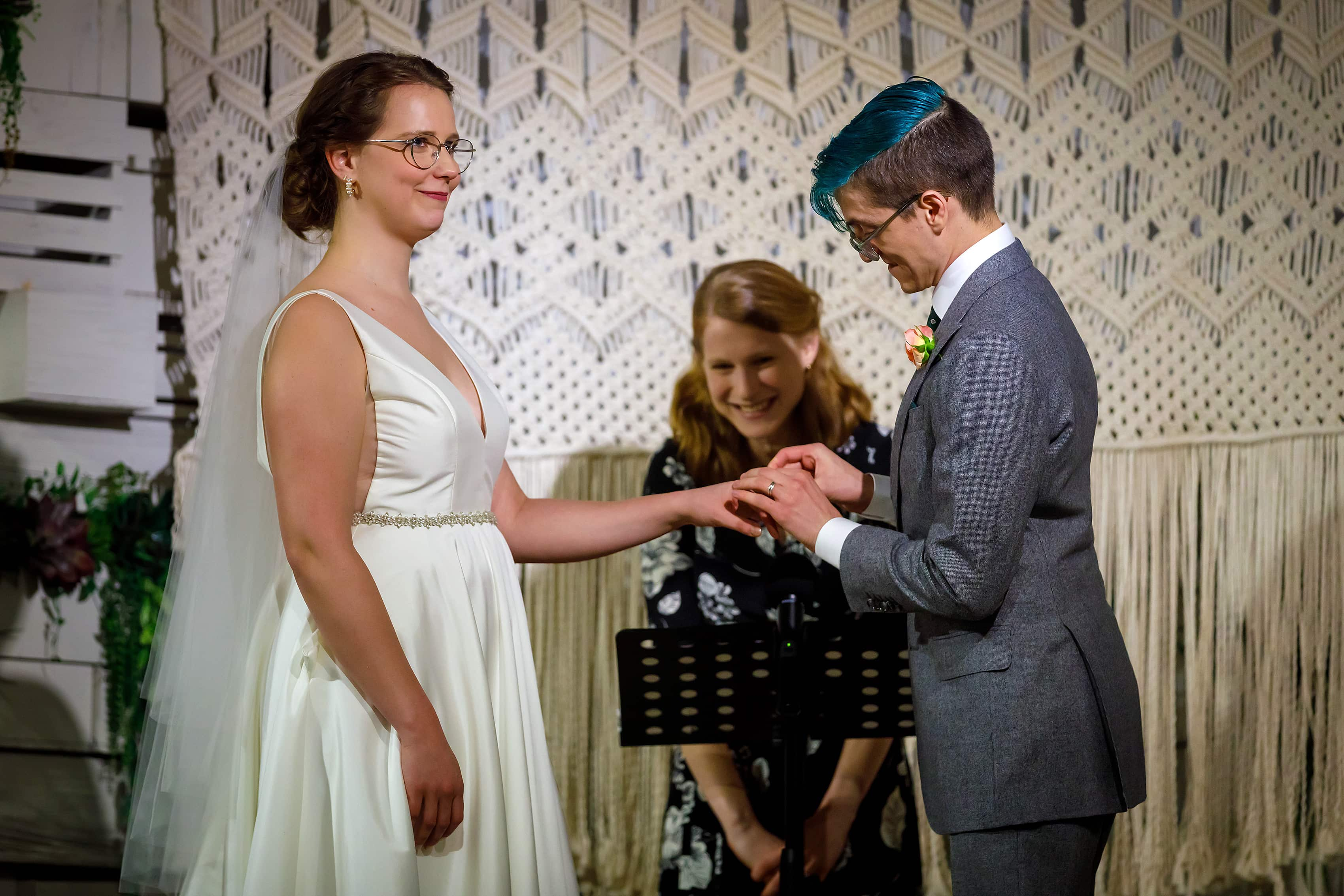 bride and groom exchange rings during wedding ceremony at Rust Belt Market in downtown Ferndale, Michigan