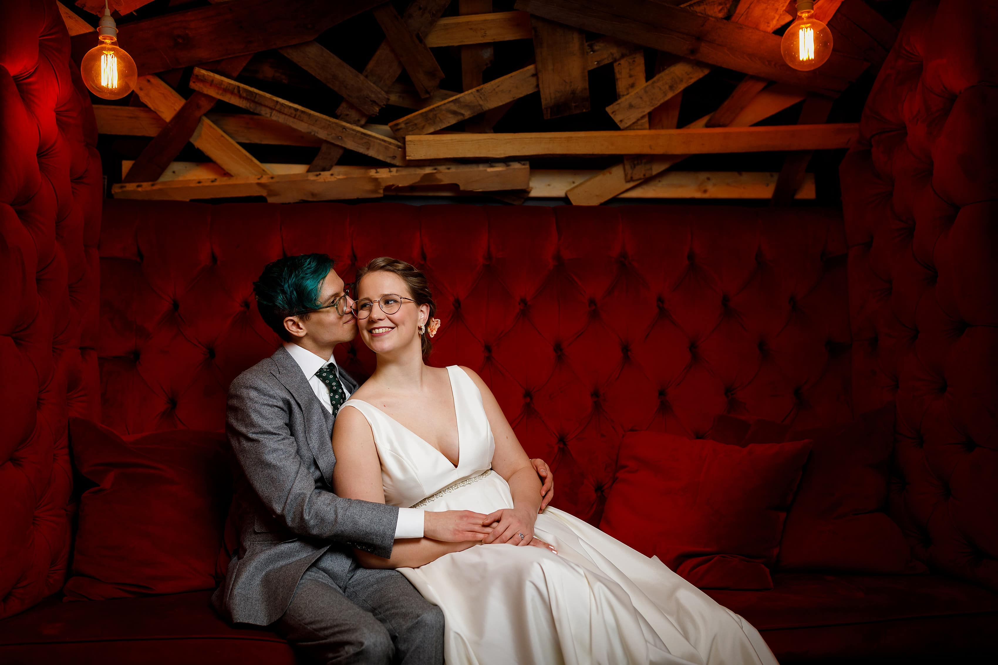 wedding portrait on red couch at Rust Belt Market in downtown Ferndale, Michigan