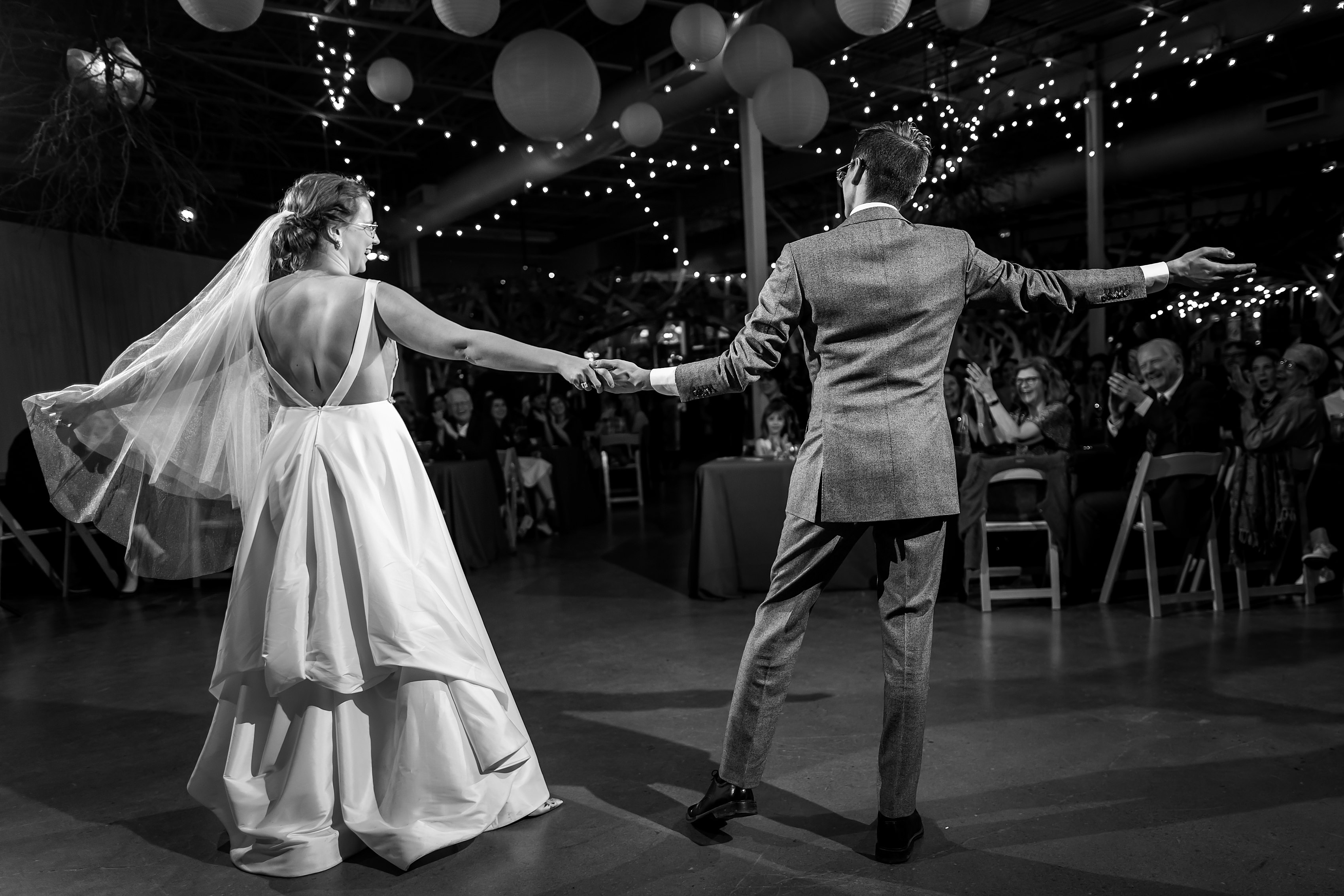 black and white first dance with bride and groom doing choreographed spin to audience during wedding reception at Rust Belt Market in downtown Ferndale, Michigan