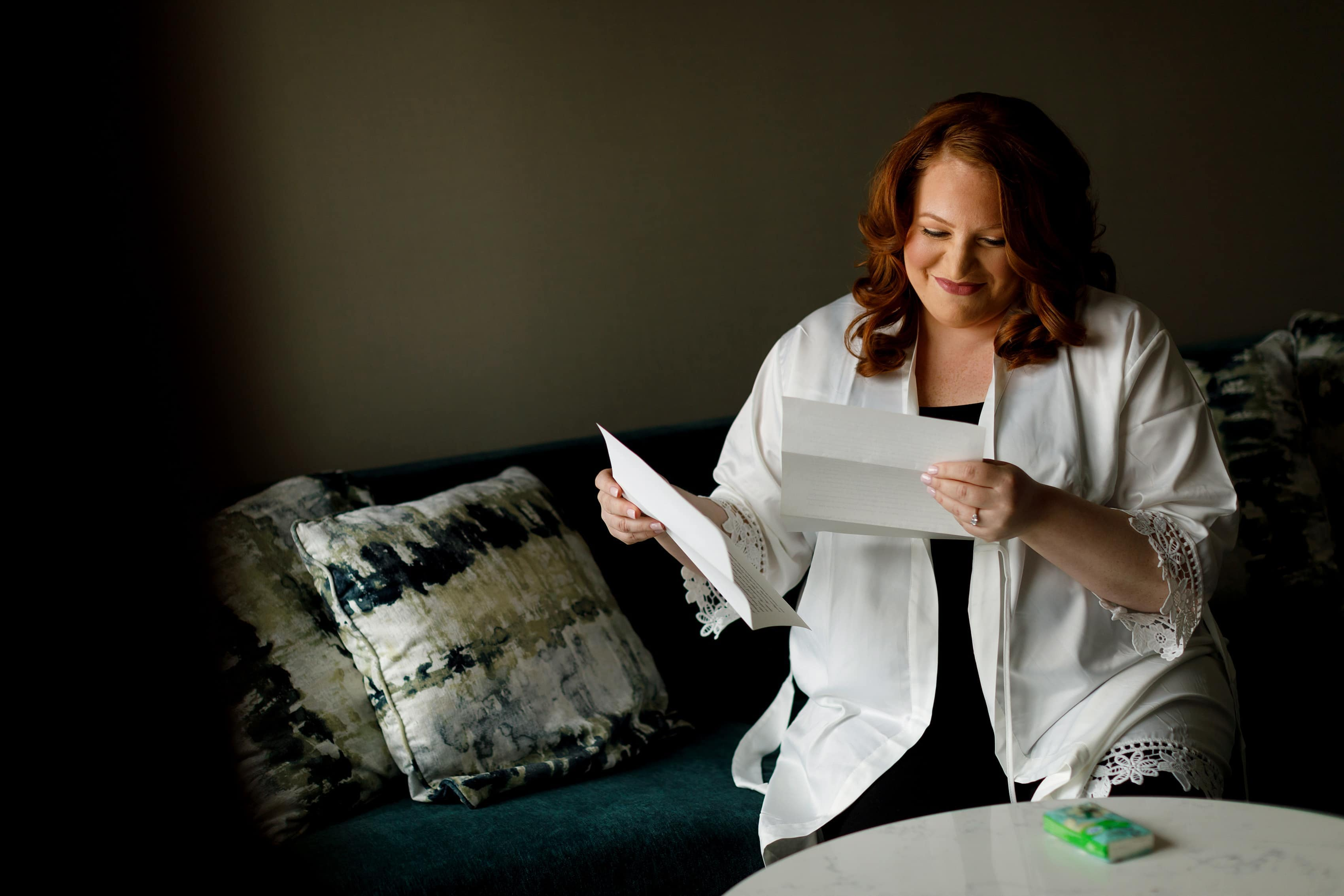 bride reads letter from her husband to be while getting ready for her wedding