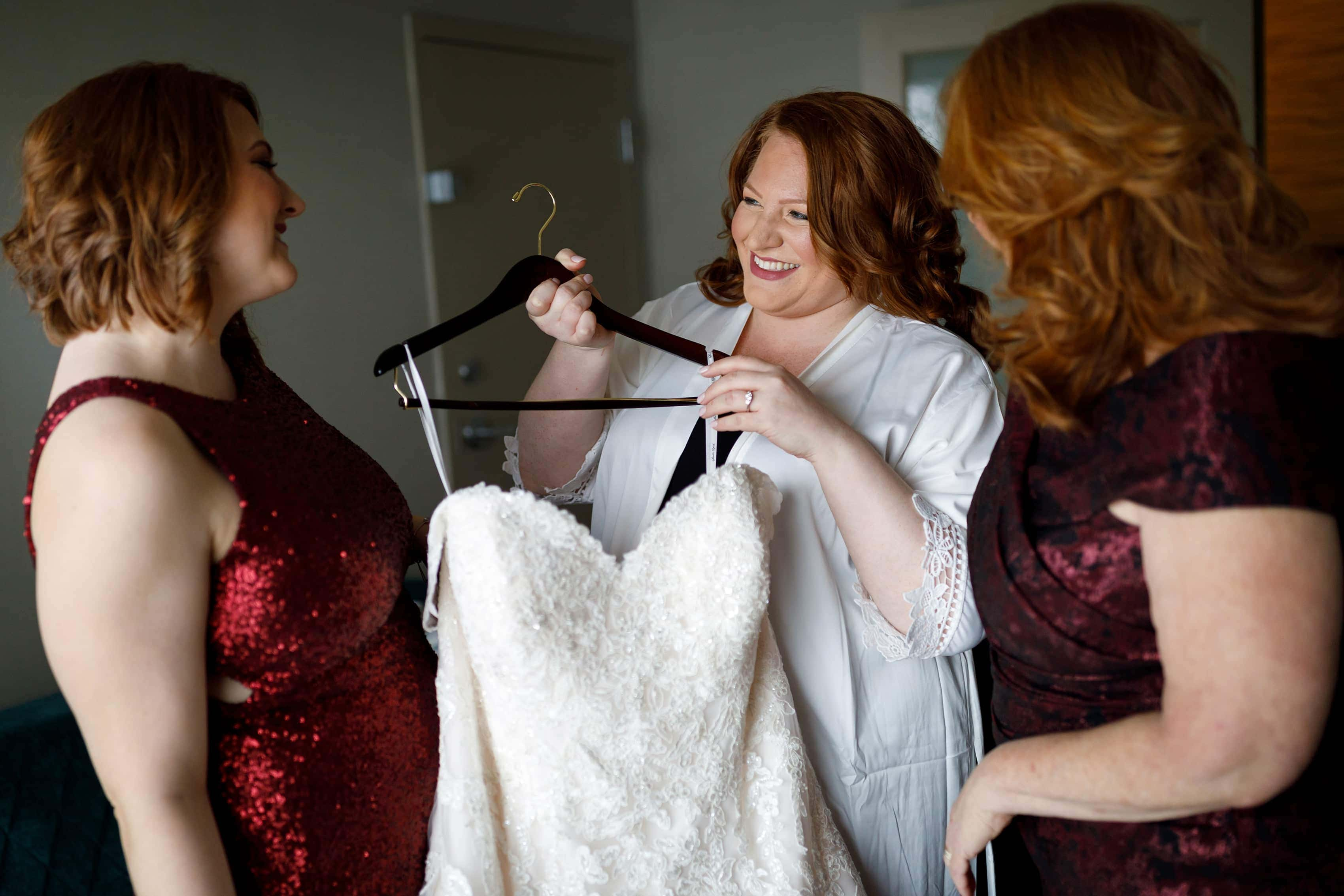 bride holds wedding dress with sister and mother getting ready for her wedding