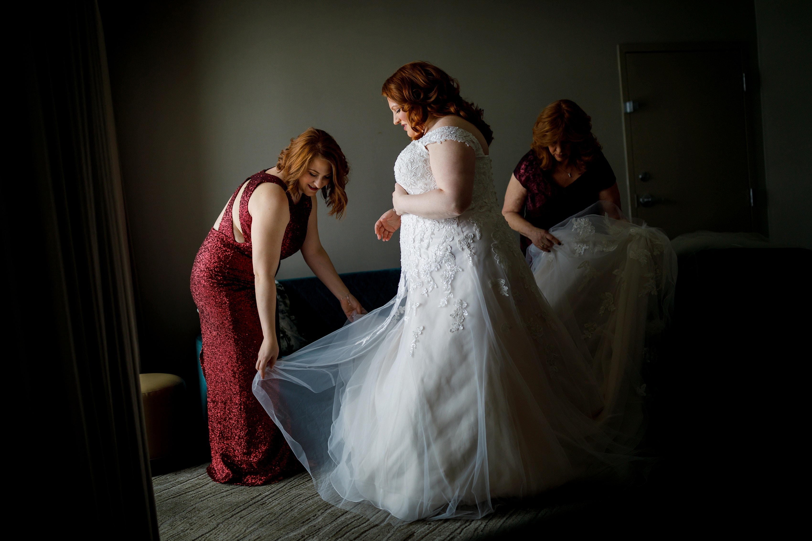 sister and mother help bride with wedding dress