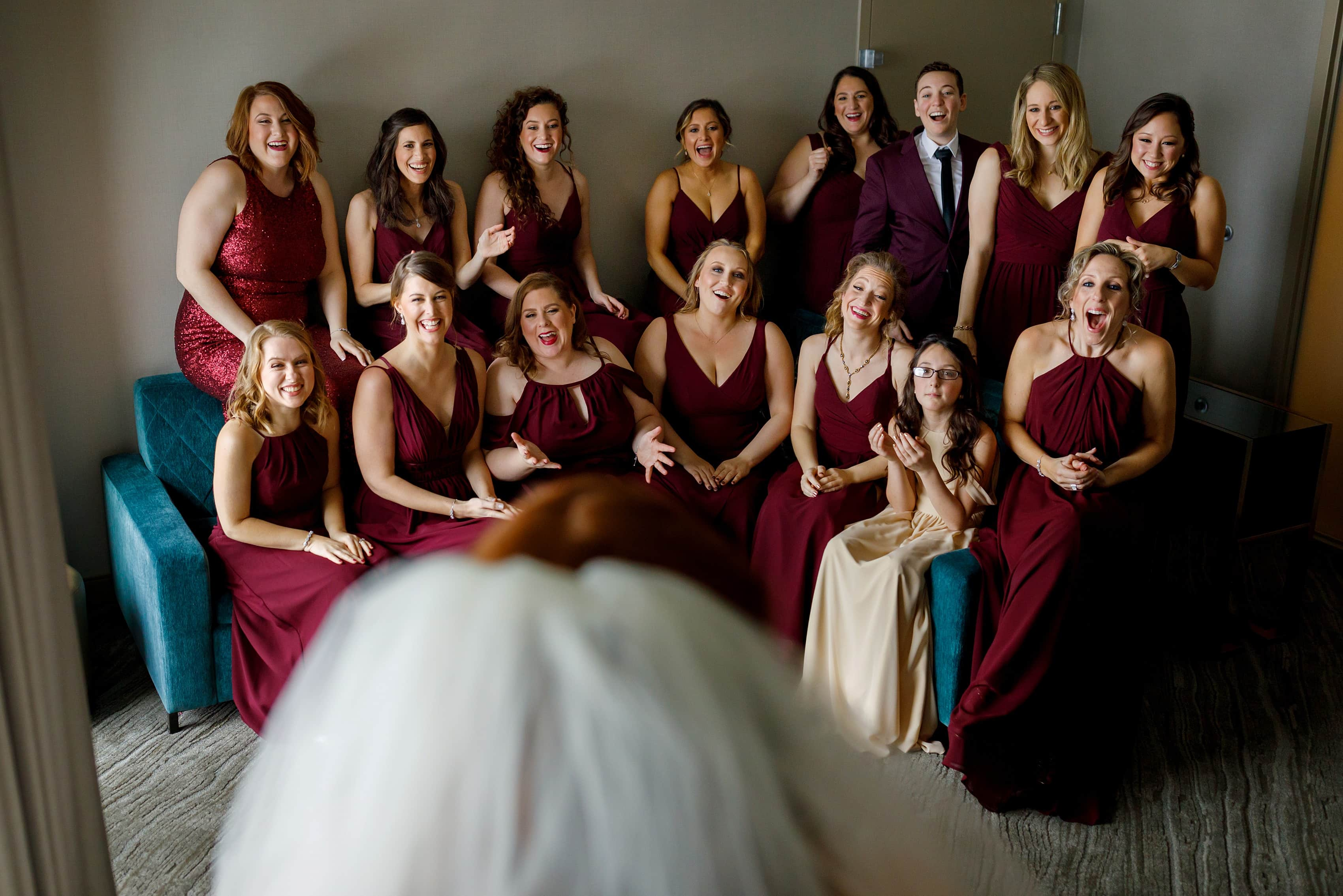 huge group of bridesmaids react to seeing bride in her wedding dress