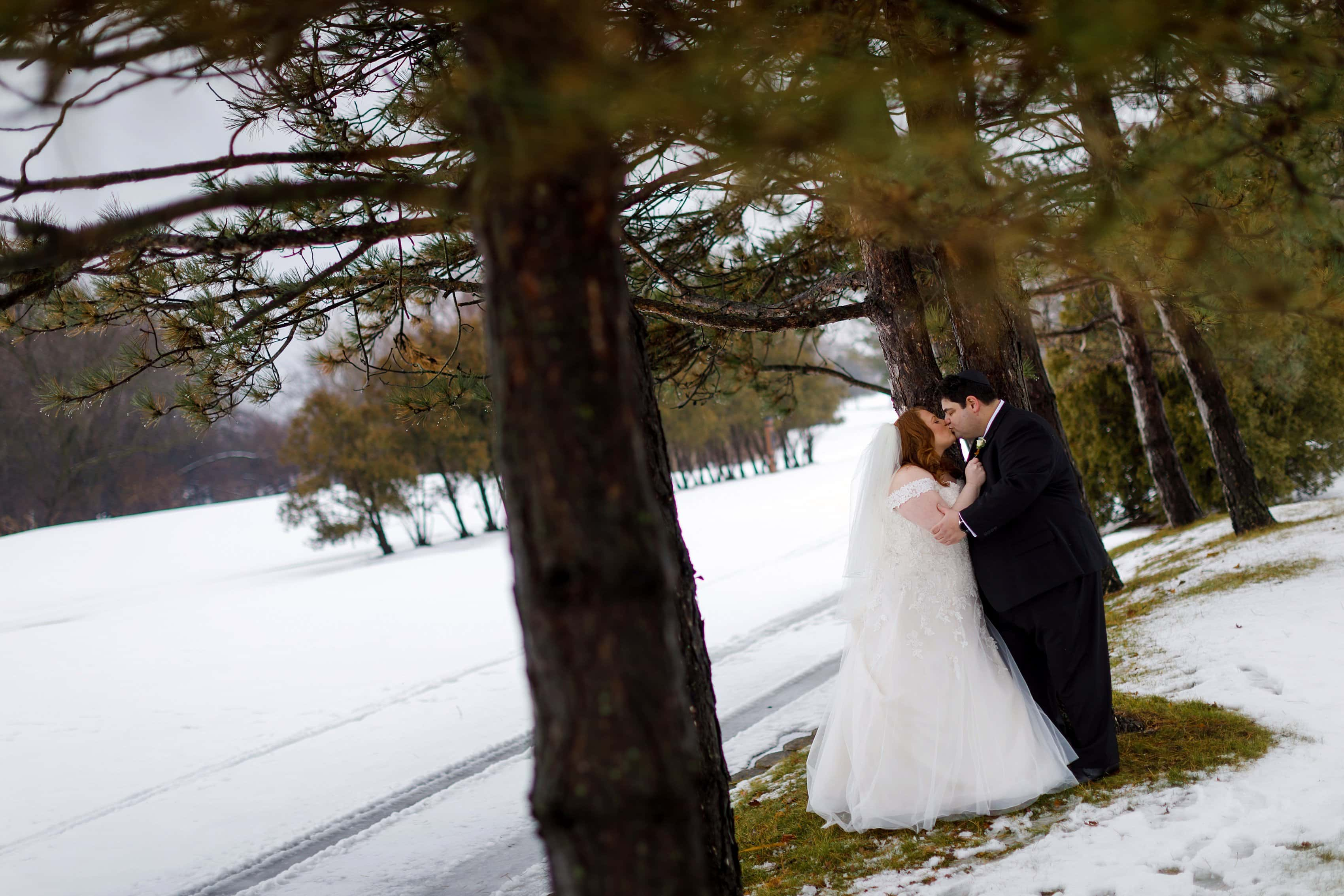 bride and groom kiss under pine tree branches during winter wedding at Lincolnshire Marriott Resort