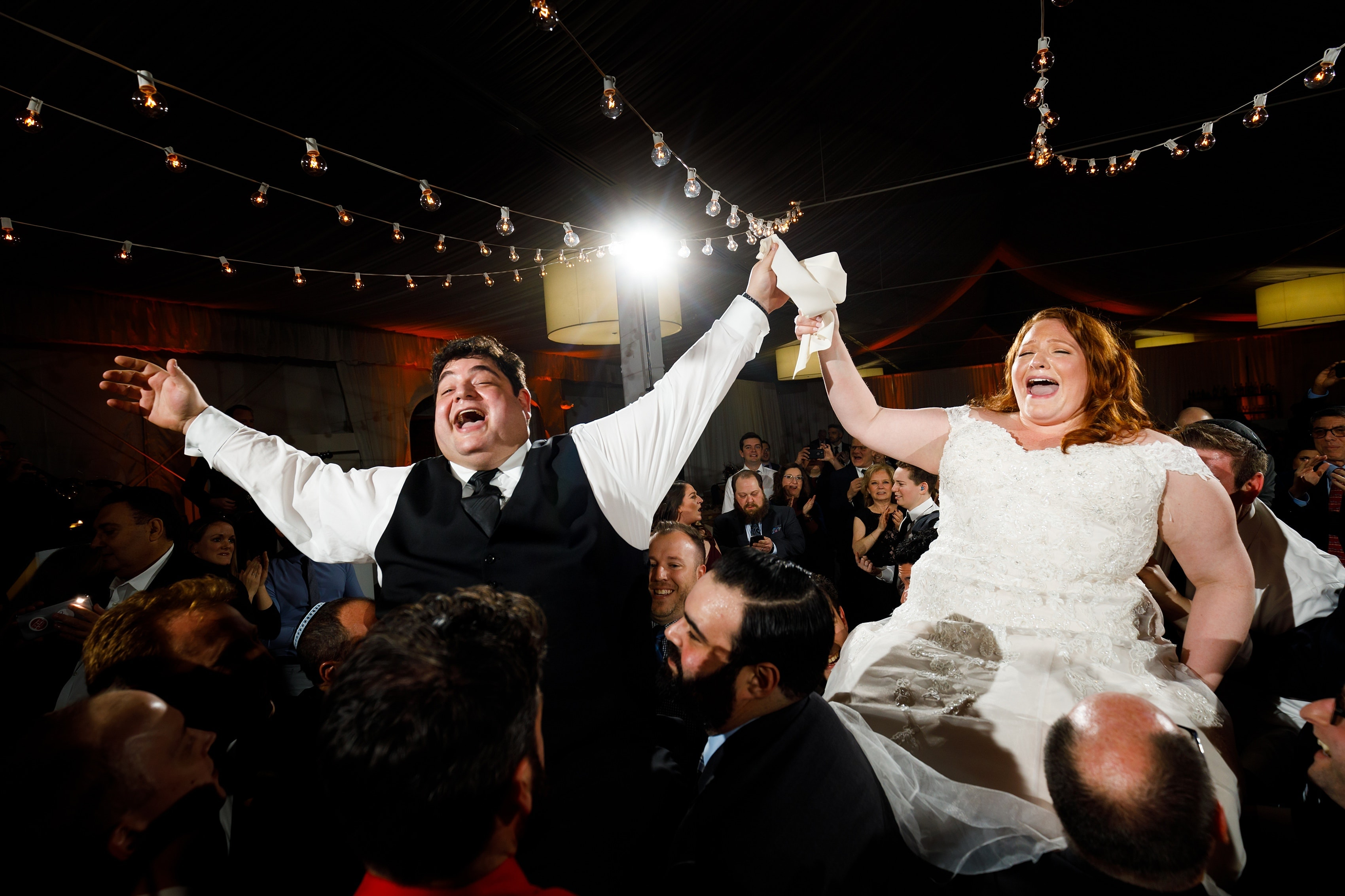 bride and groom are lifted on chairs during hora dance of Lincolnshire Marriott Resort wedding reception