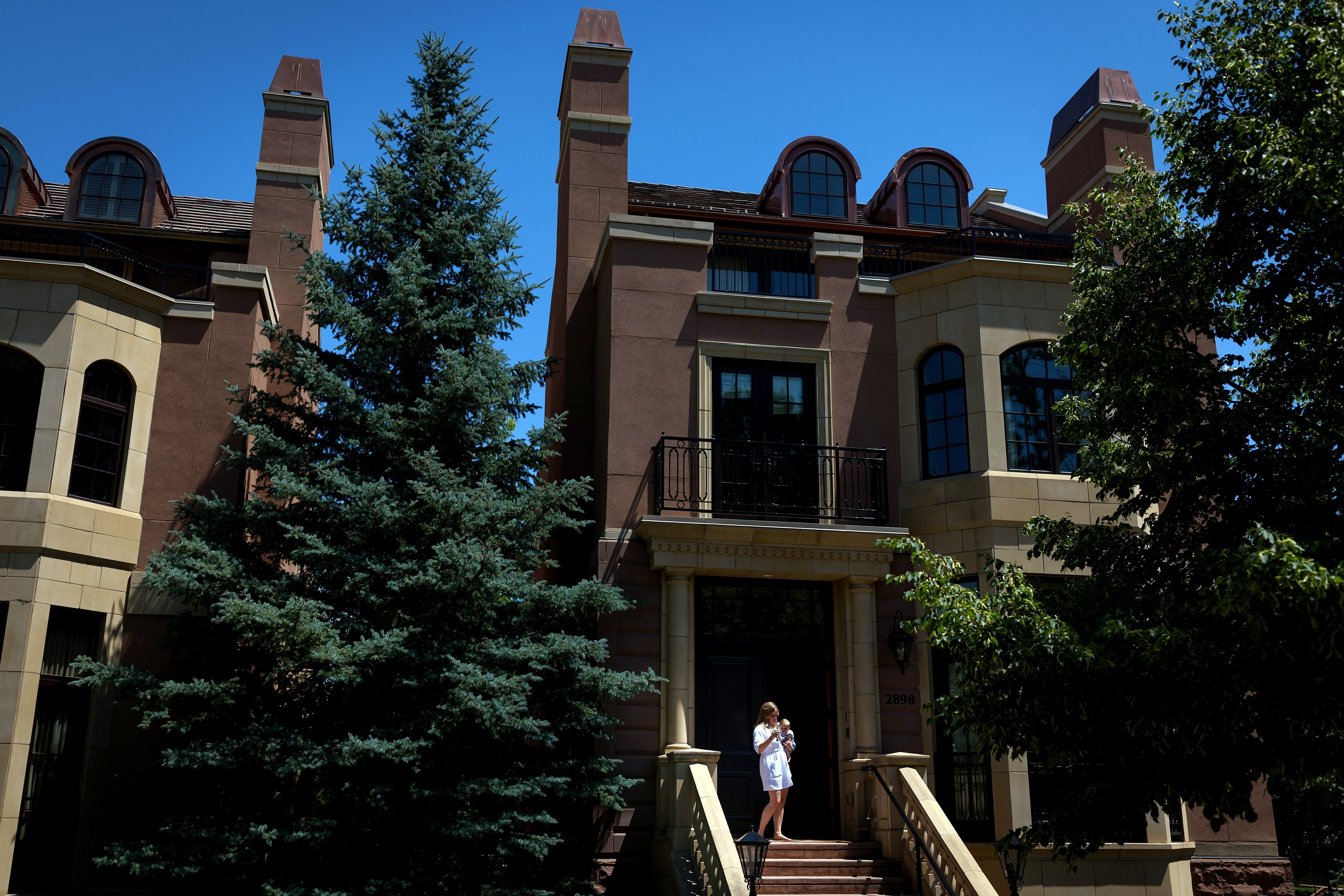 bride stands on steps at the tonwhomes at The Broadmoor Resort in Colorado Springs while getting ready for her wedding