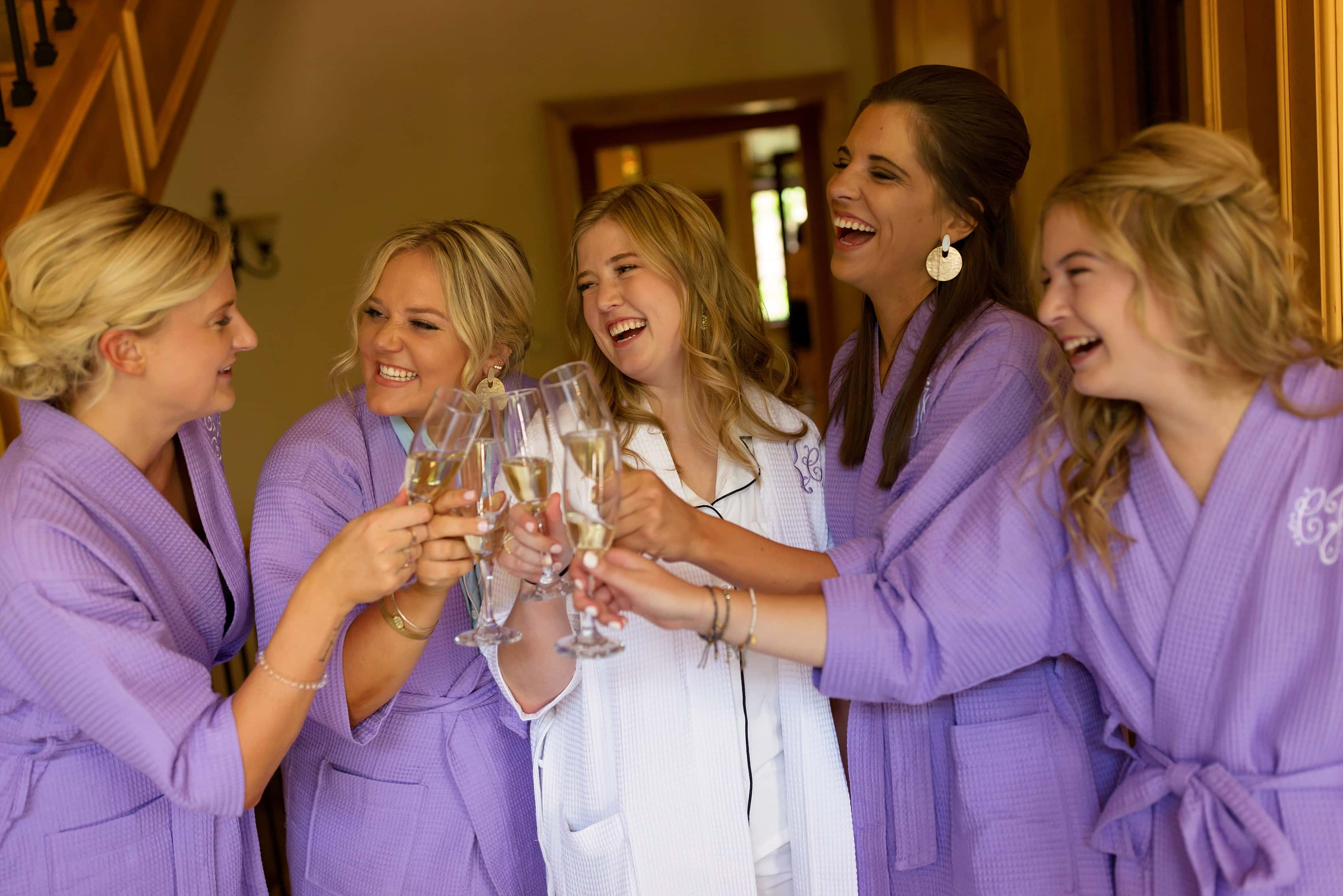 bride toasts with bridesmaids while getting ready for her wedding