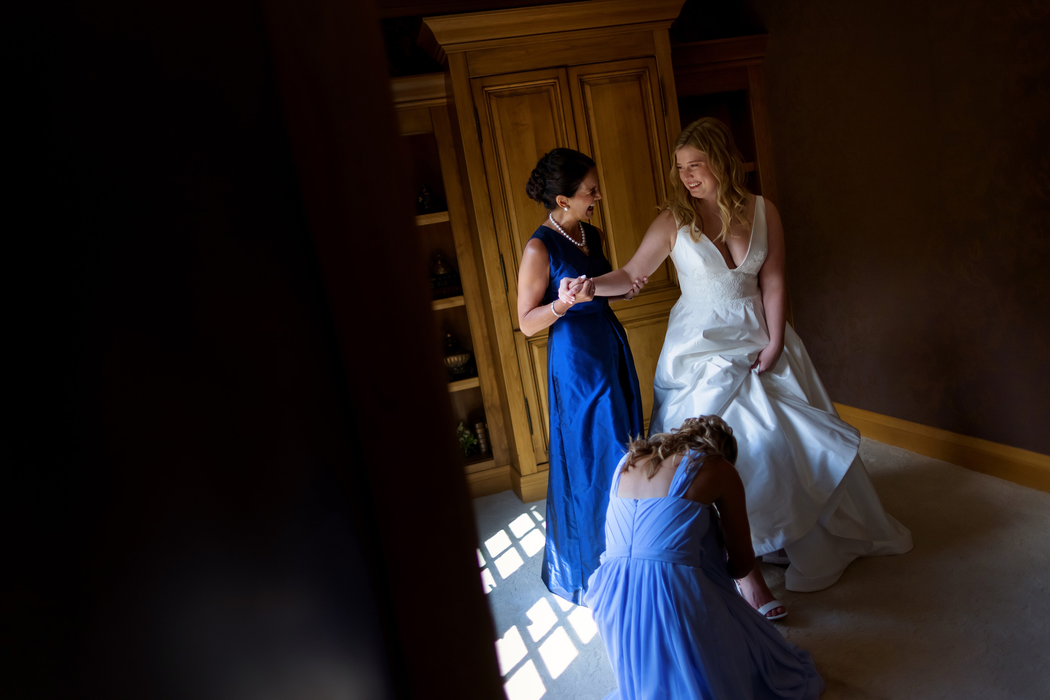 mother of bride and sister help bride into dress while getting ready