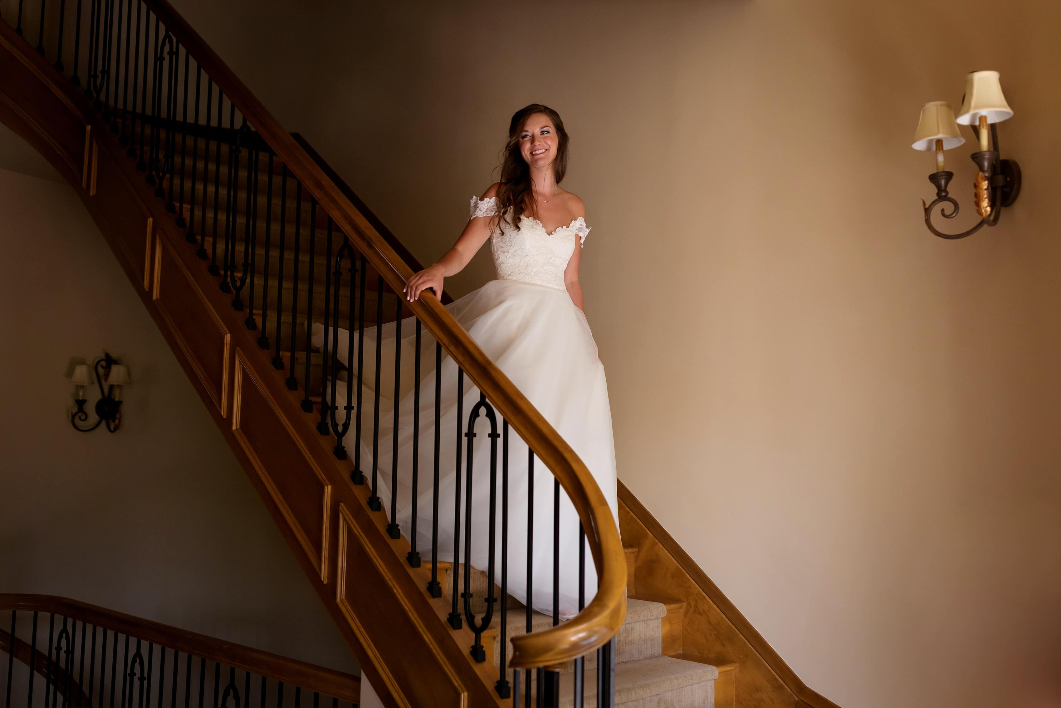 bride walks down oval stairs from above