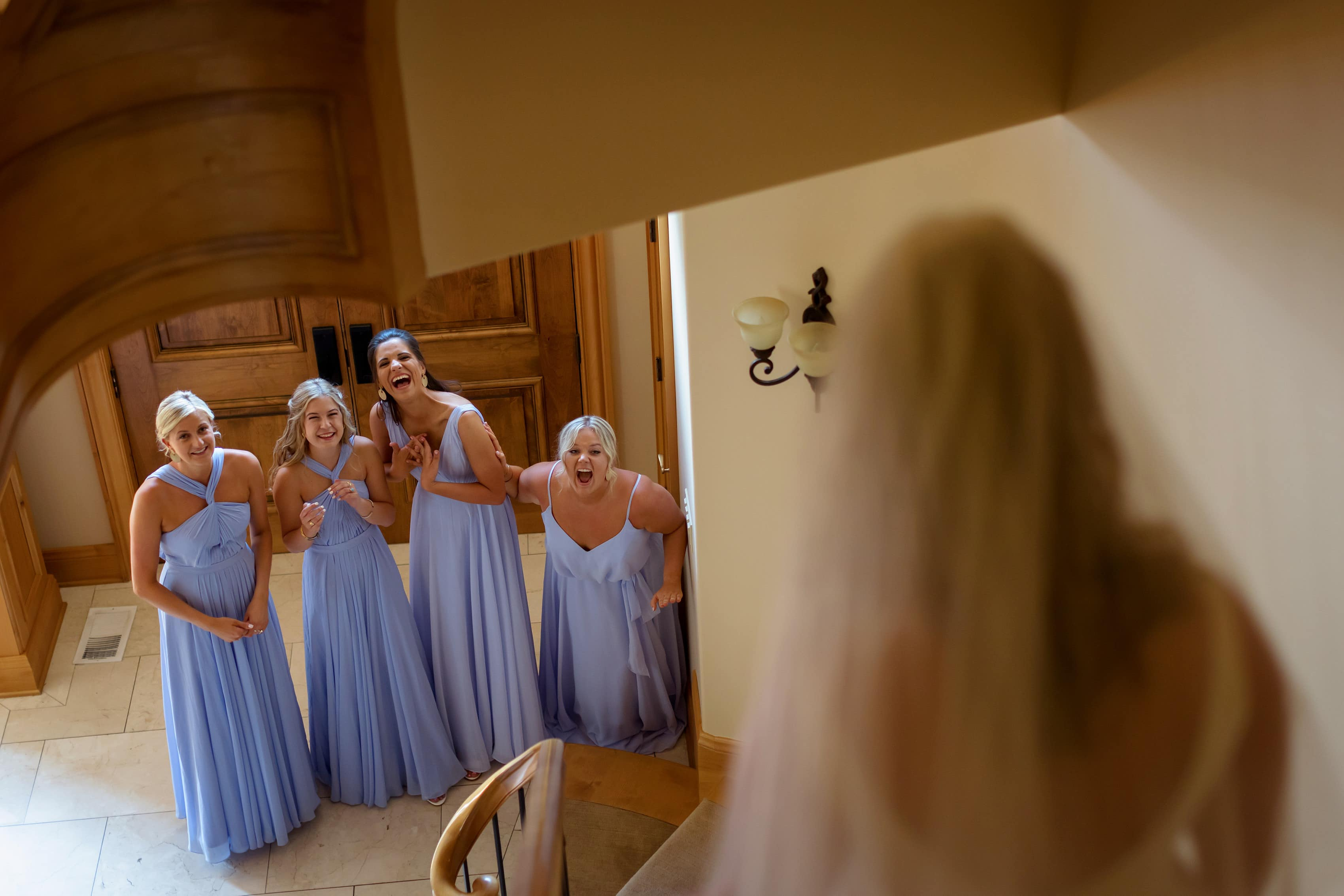bride walks down oval stairs from above with reactions of bridesmaids to her dress