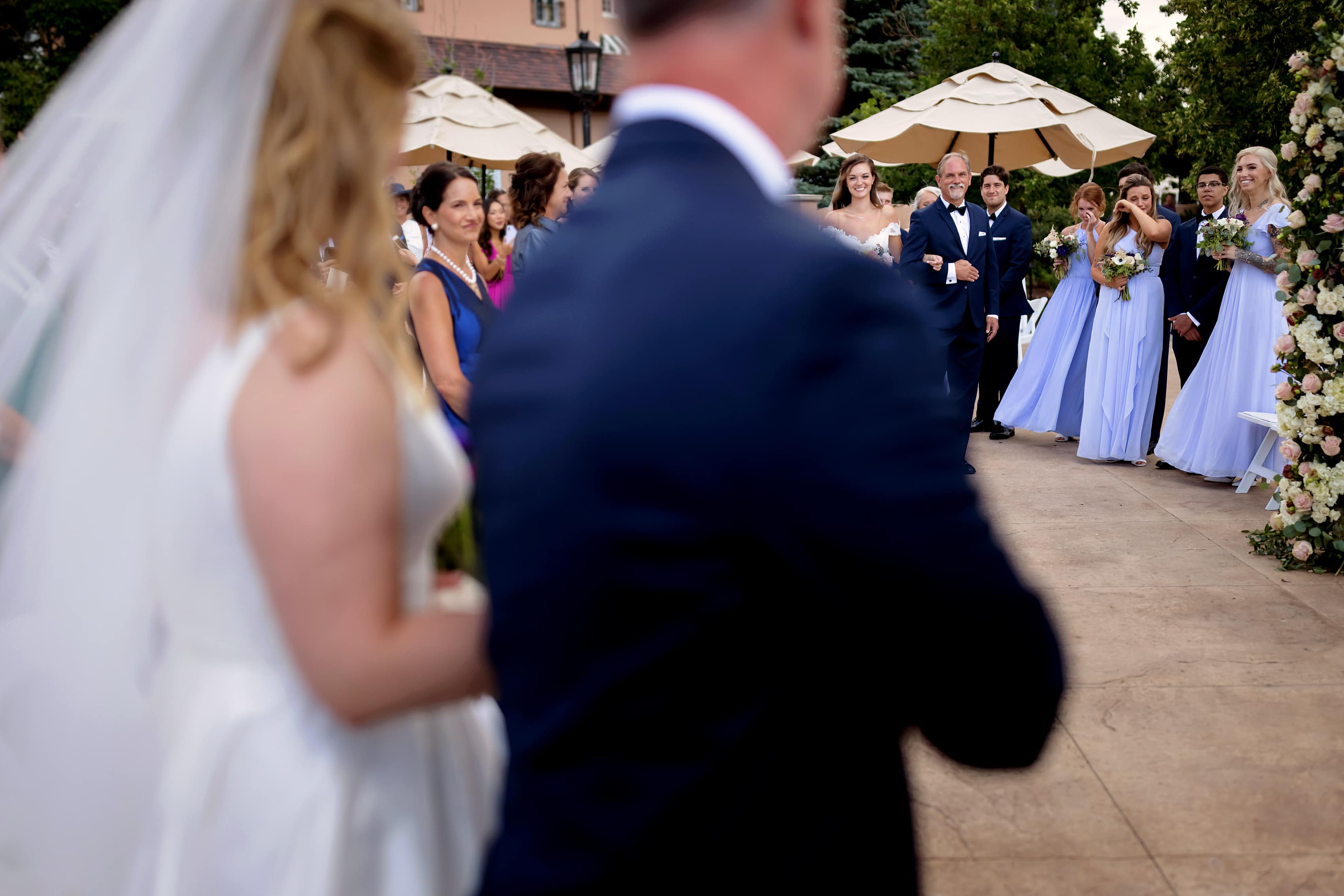 bride and her father walk down the aisle during wedding at The Broadmoor in Colorado Springs, Colorado