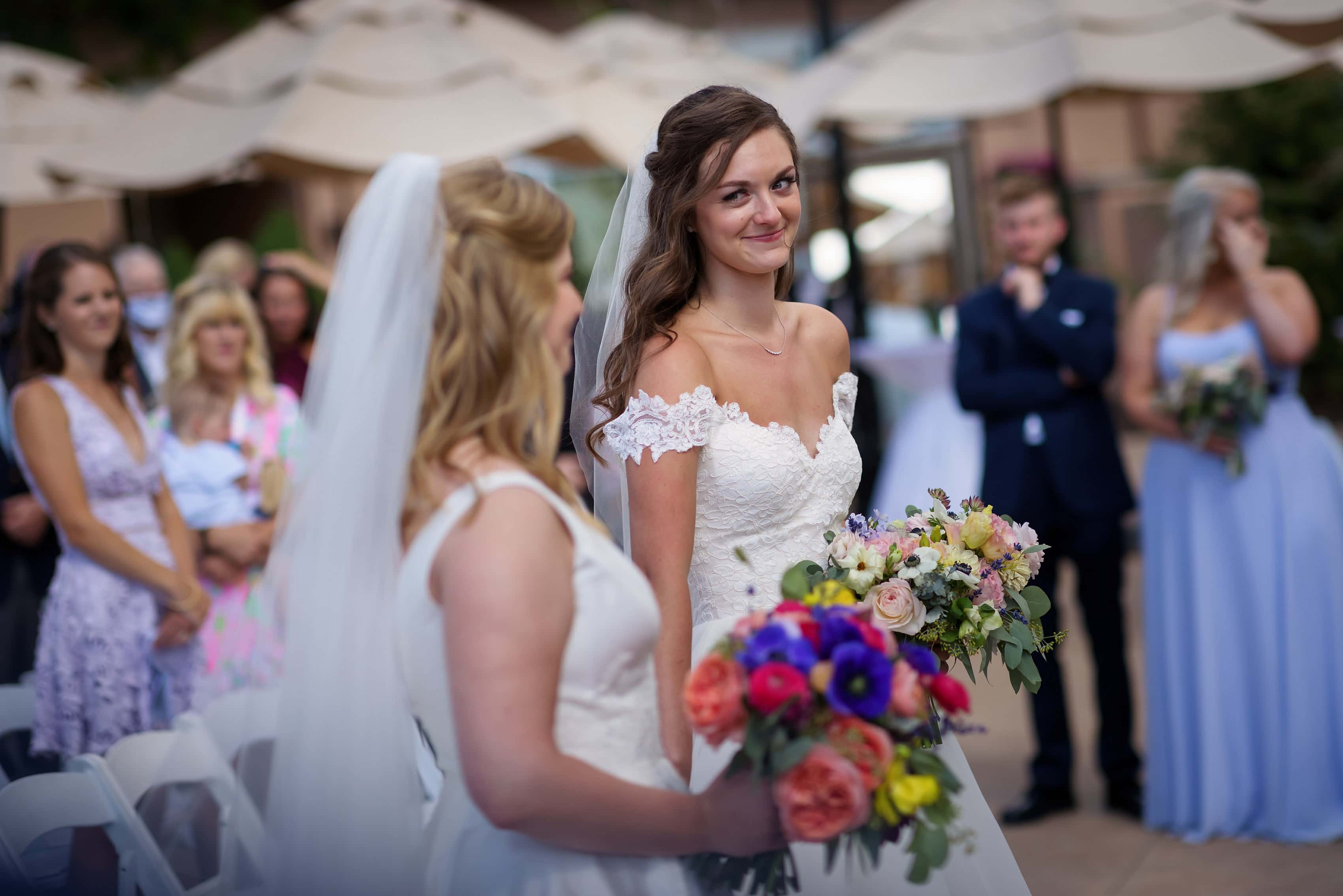 brides look at each other during wedding ceremony with two brides at The Broadmoor in Colorado Springs, Colorado