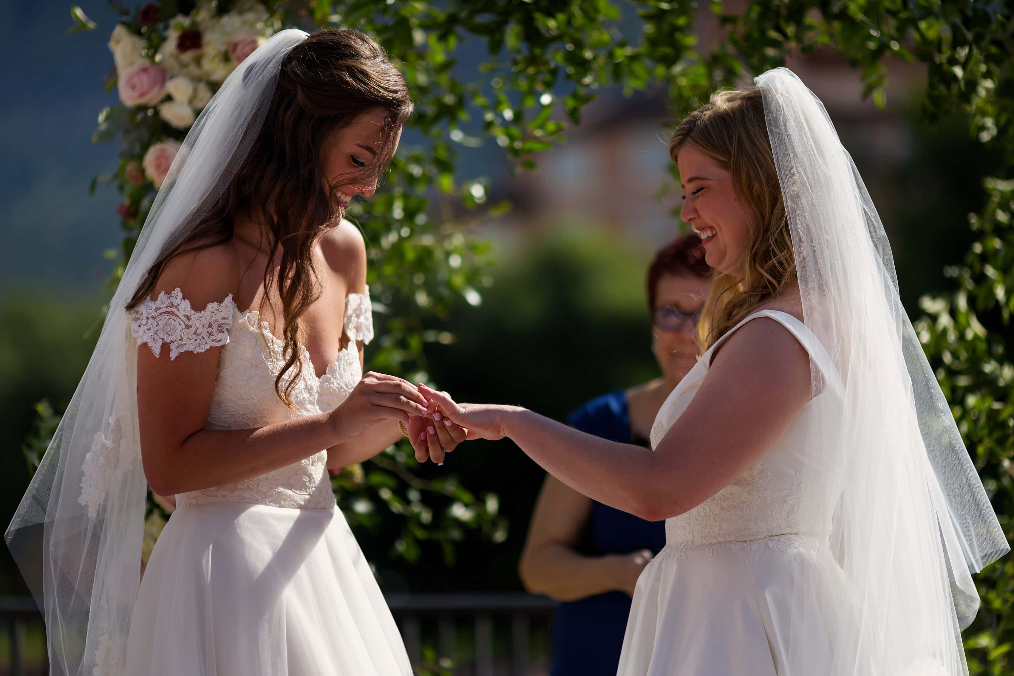 brides exchange rings during wedding ceremony with two brides at The Broadmoor in Colorado Springs, Colorado