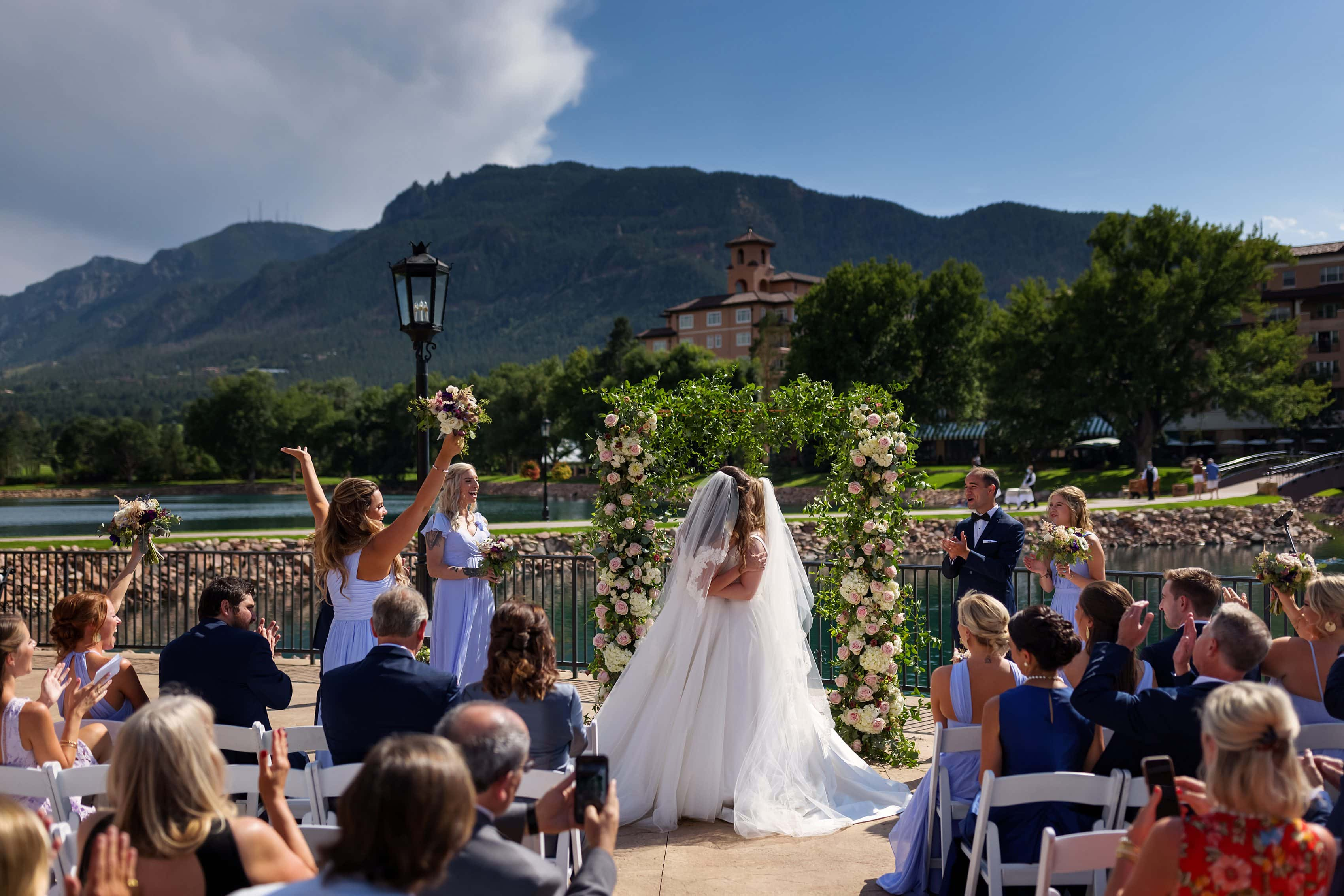 two brides share a kiss during wedding ceremony at The Broadmoor in Colorado Springs, Colorado