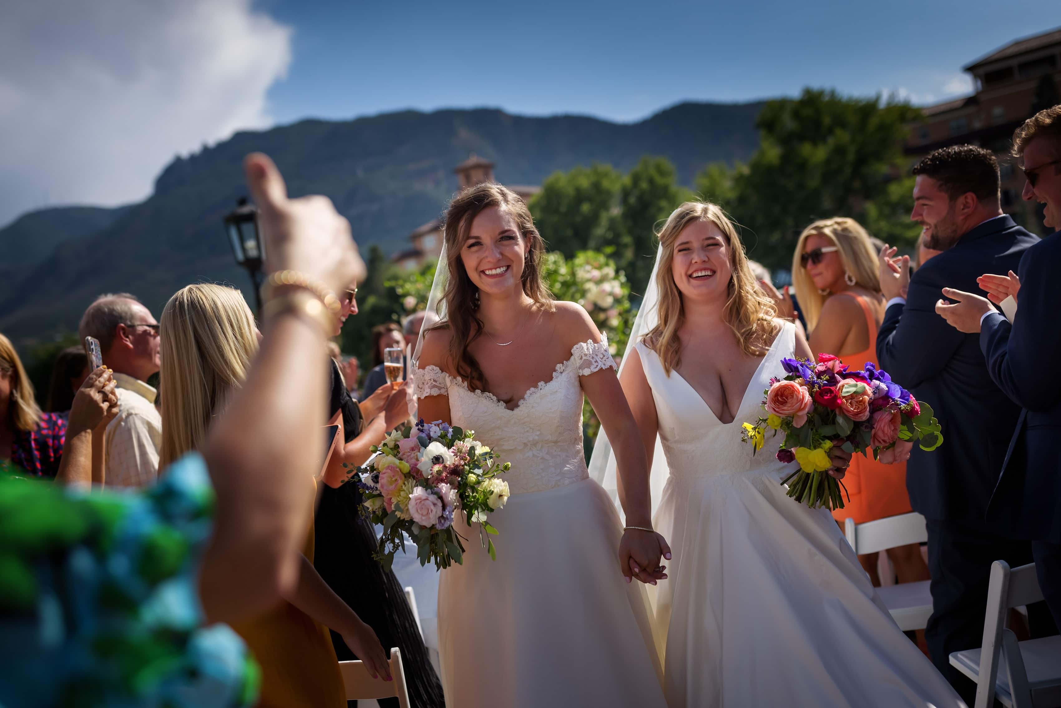 two brides walk down the aisle after their wedding ceremony at The Broadmoor in Colorado Springs, Colorado