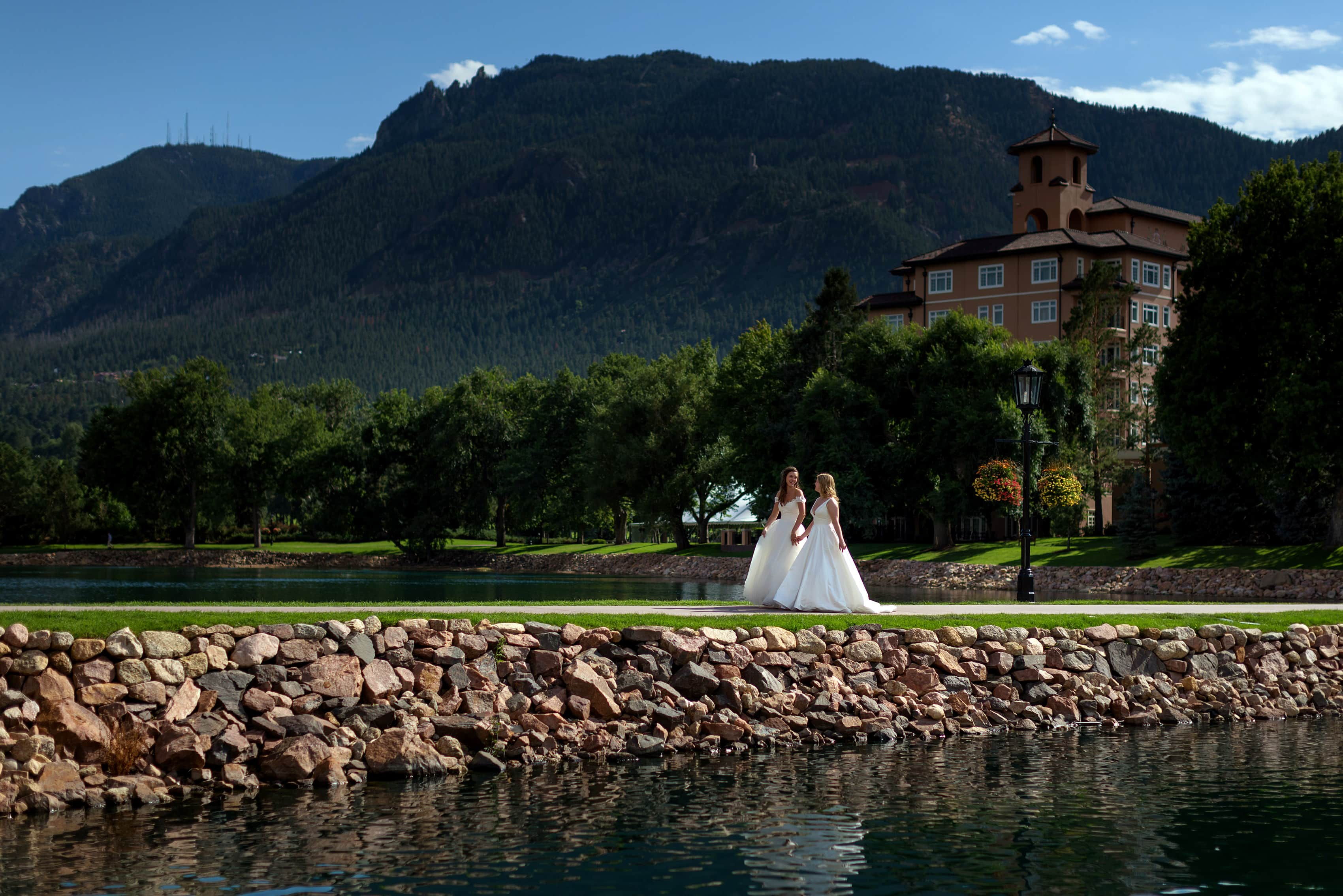 two brides walk together for wedding portraits at The Broadmoor in Colorado Springs, Colorado