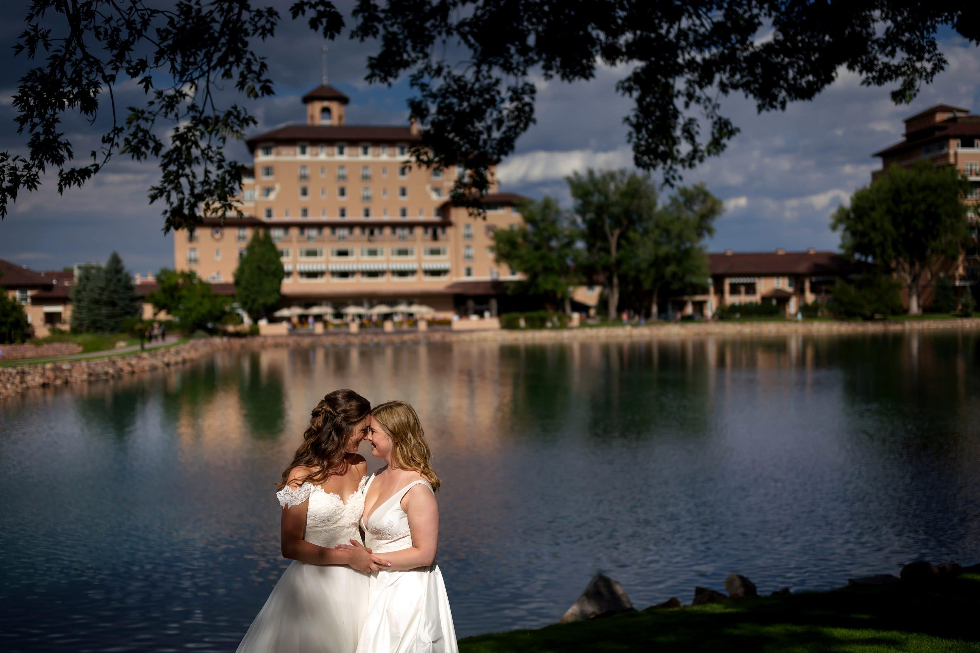 two brides pose together for wedding portraits at The Broadmoor in Colorado Springs, Colorado