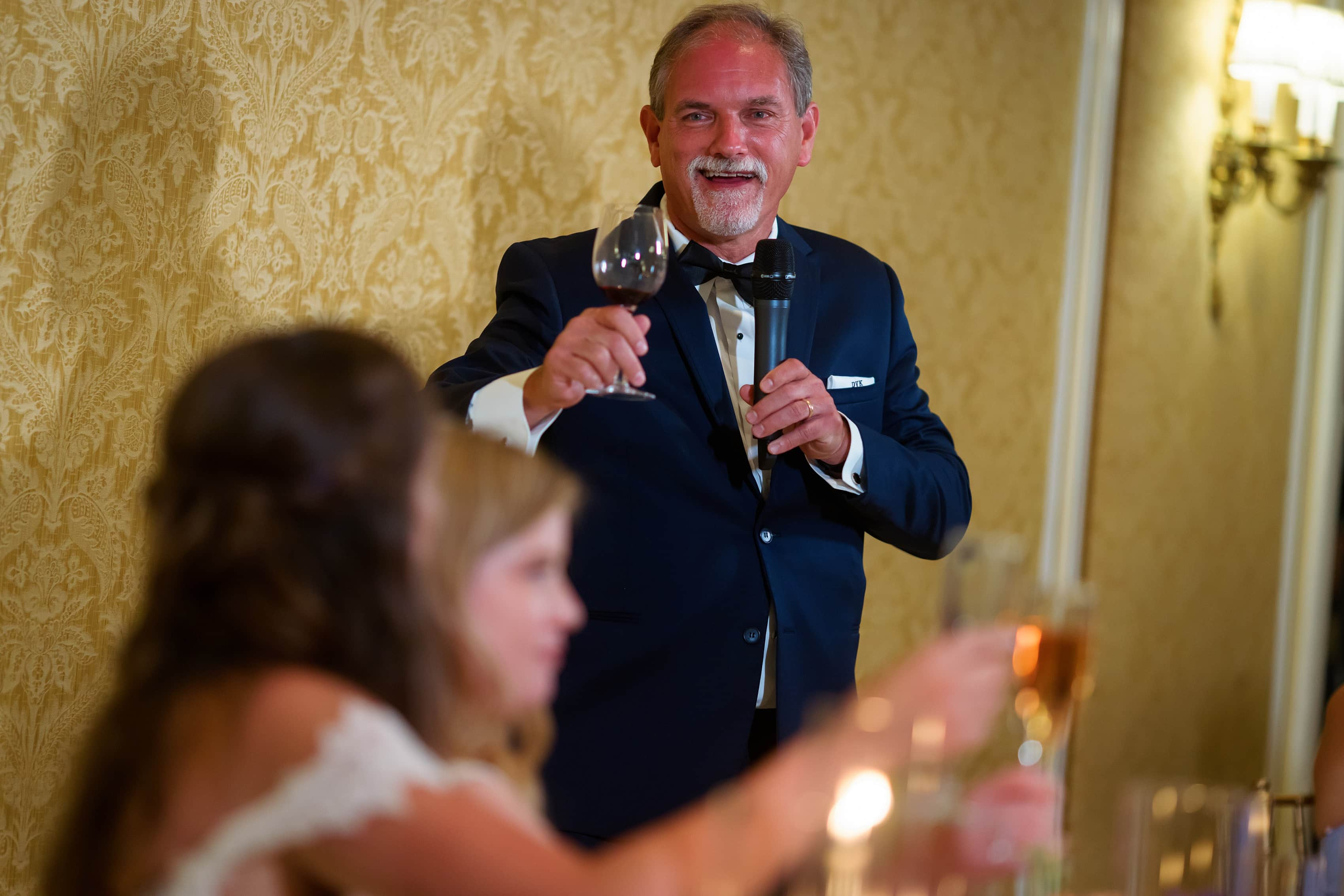 father of the bride gives toast during wedding reception