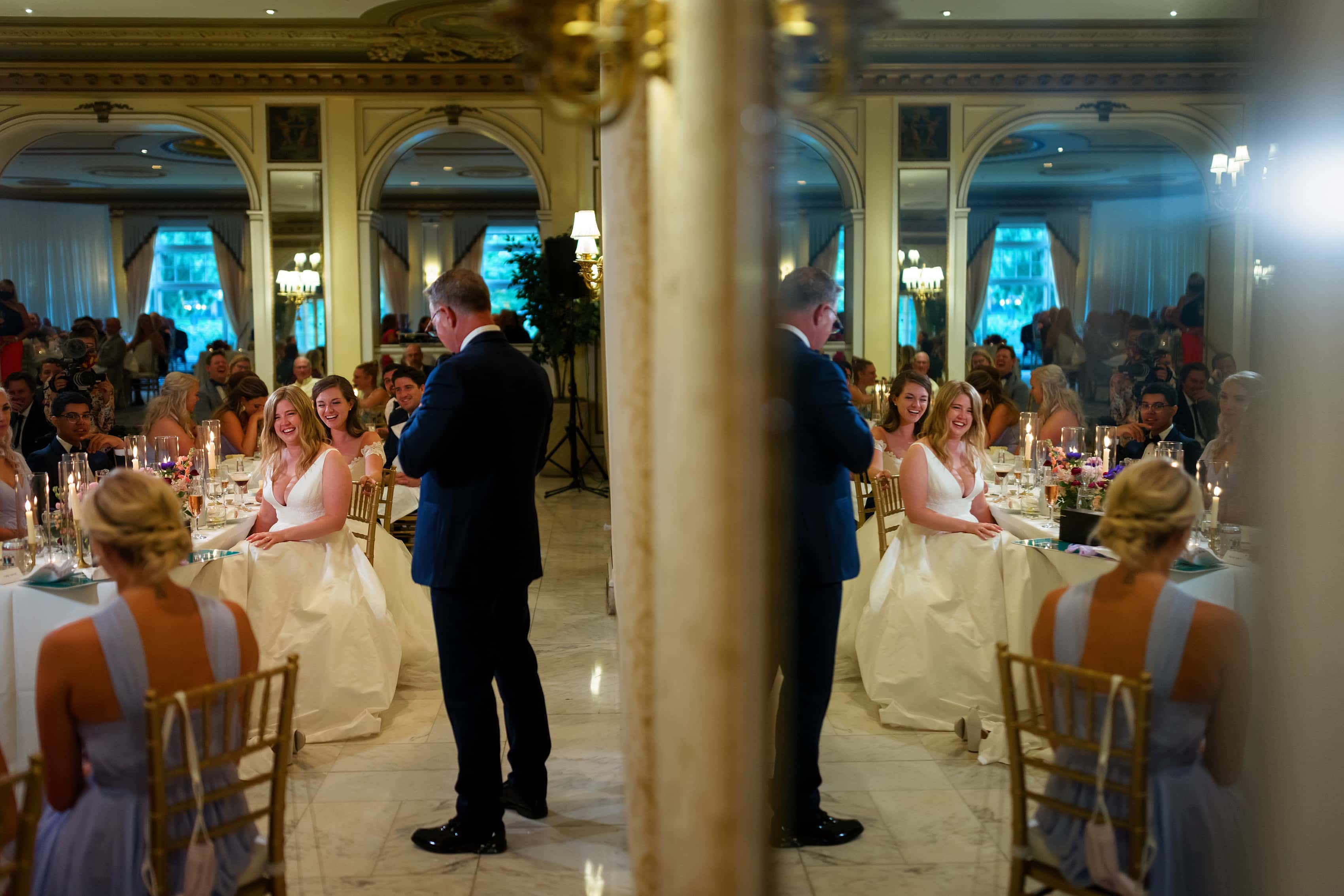 father of the bride gives toast during wedding reception brides react during wedding reception toasts