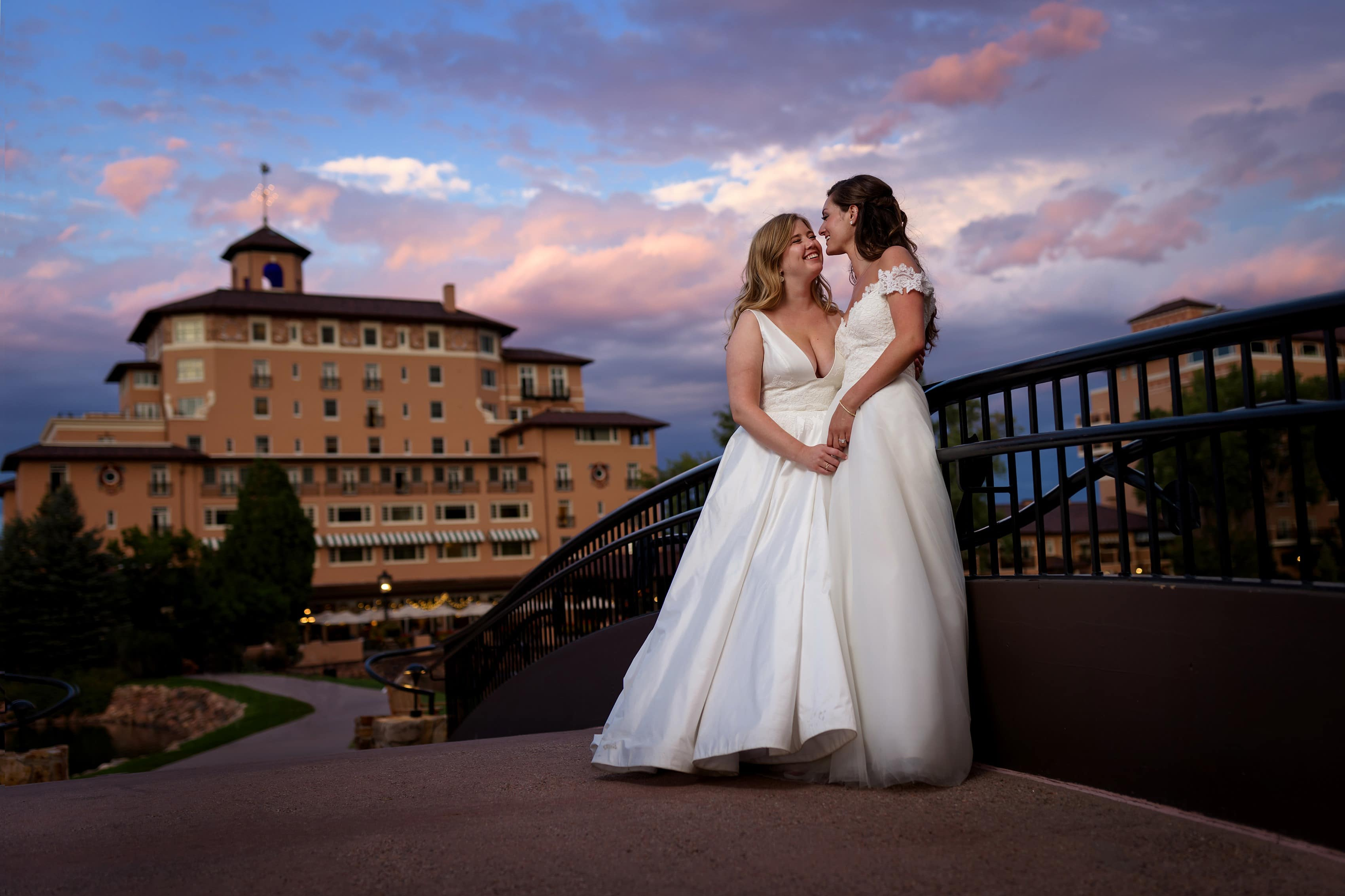 two brides pose for a portrait on the bridge at The Broadmoor Hotel during their wedding