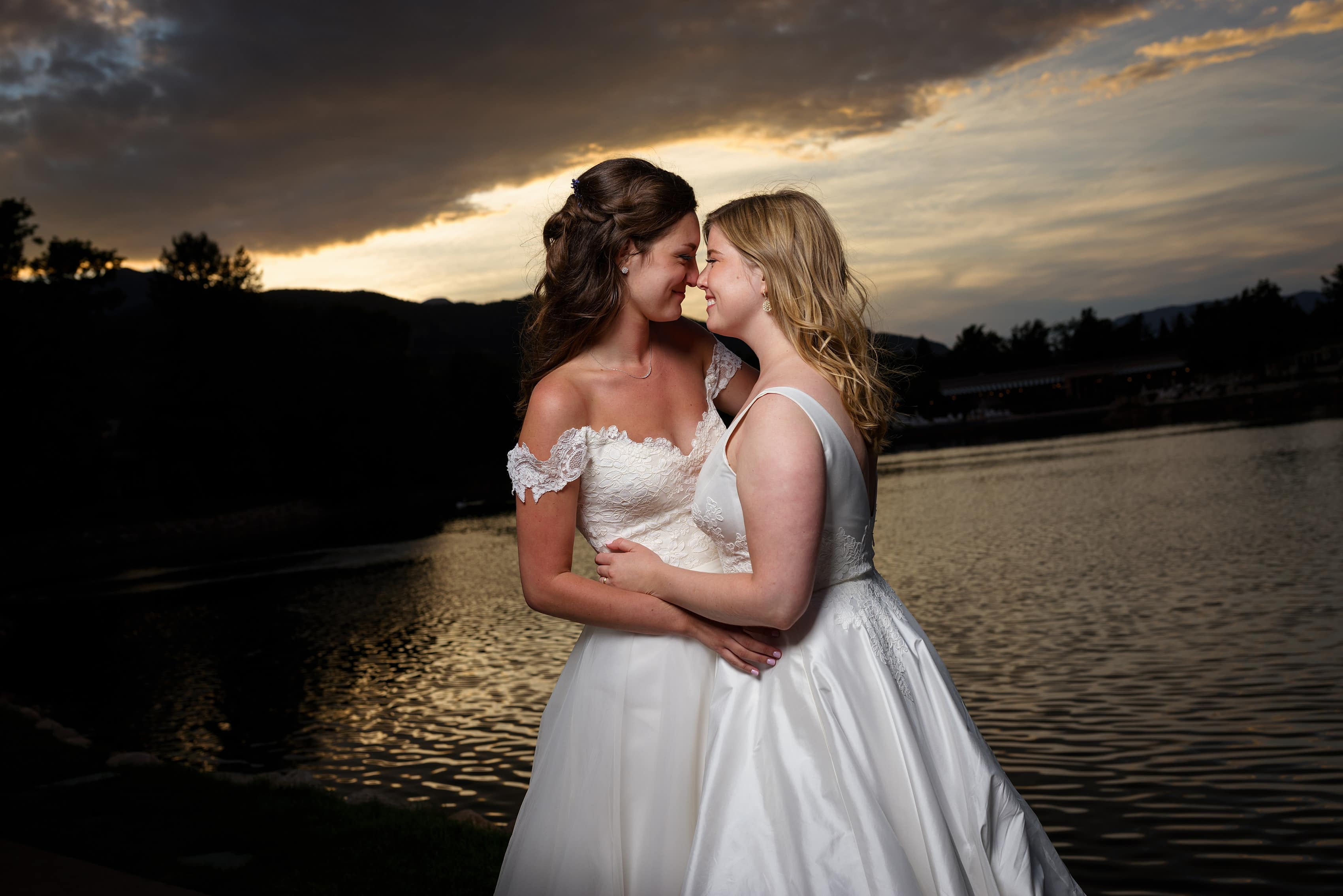 two brides pose for a sunset portrait on the bridge at The Broadmoor Hotel during their wedding