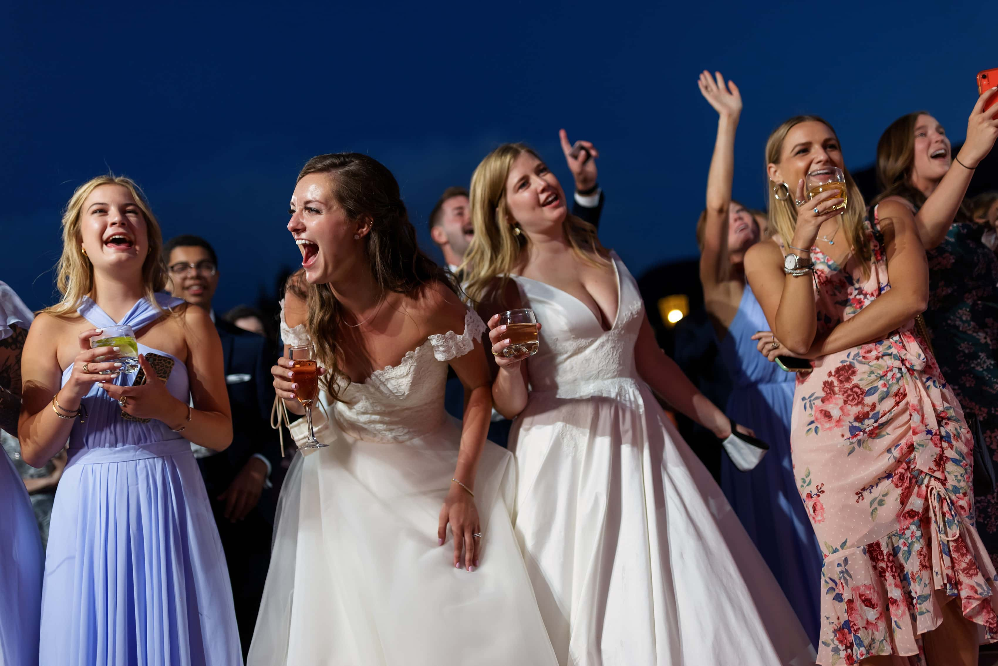 brides and guests react to a surprise musical performance by friend during wedding reception at The Broadmoor Hotel