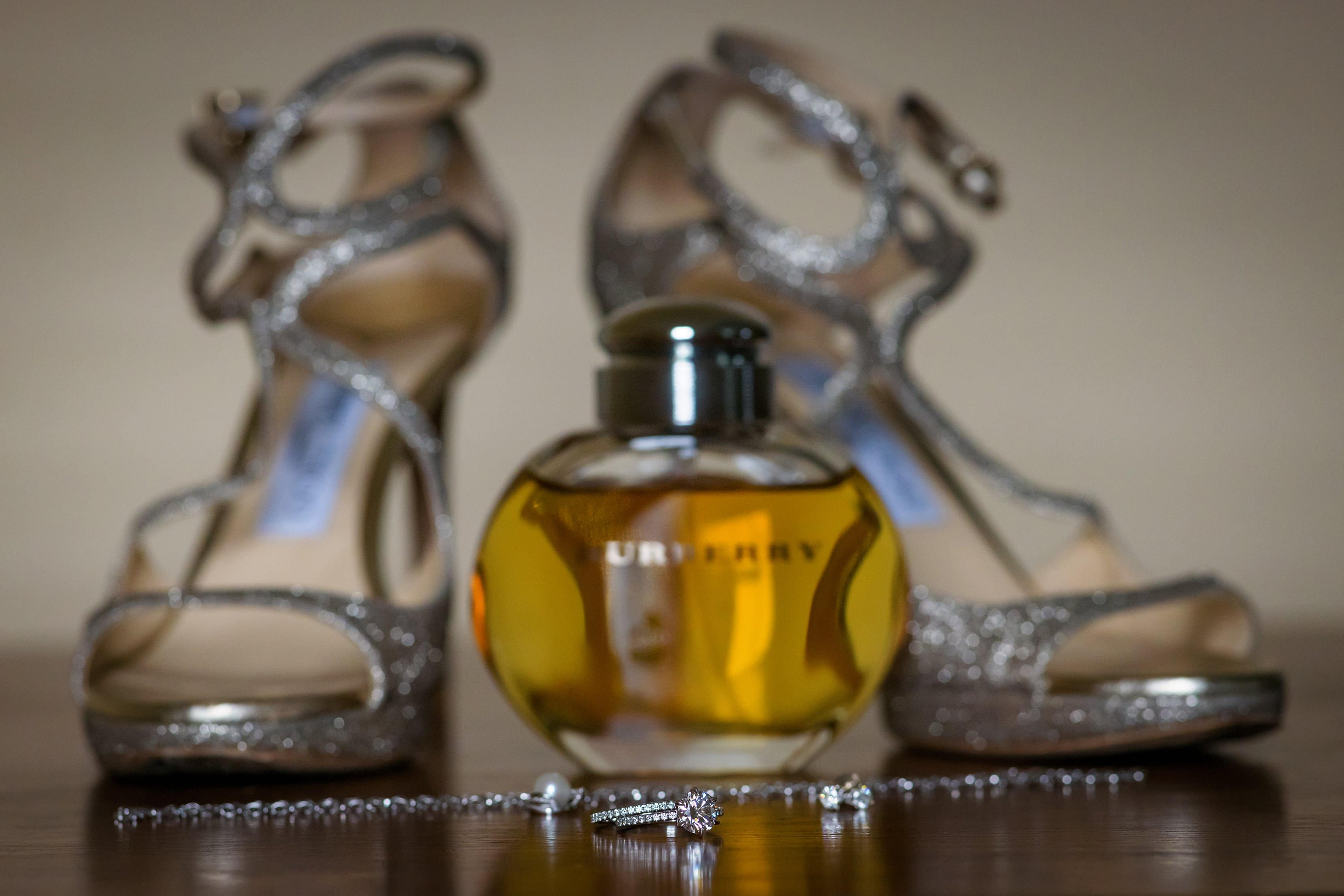 detail image of bride's Jimmy Choo shoes, rings, jewelry and Burberry perfume