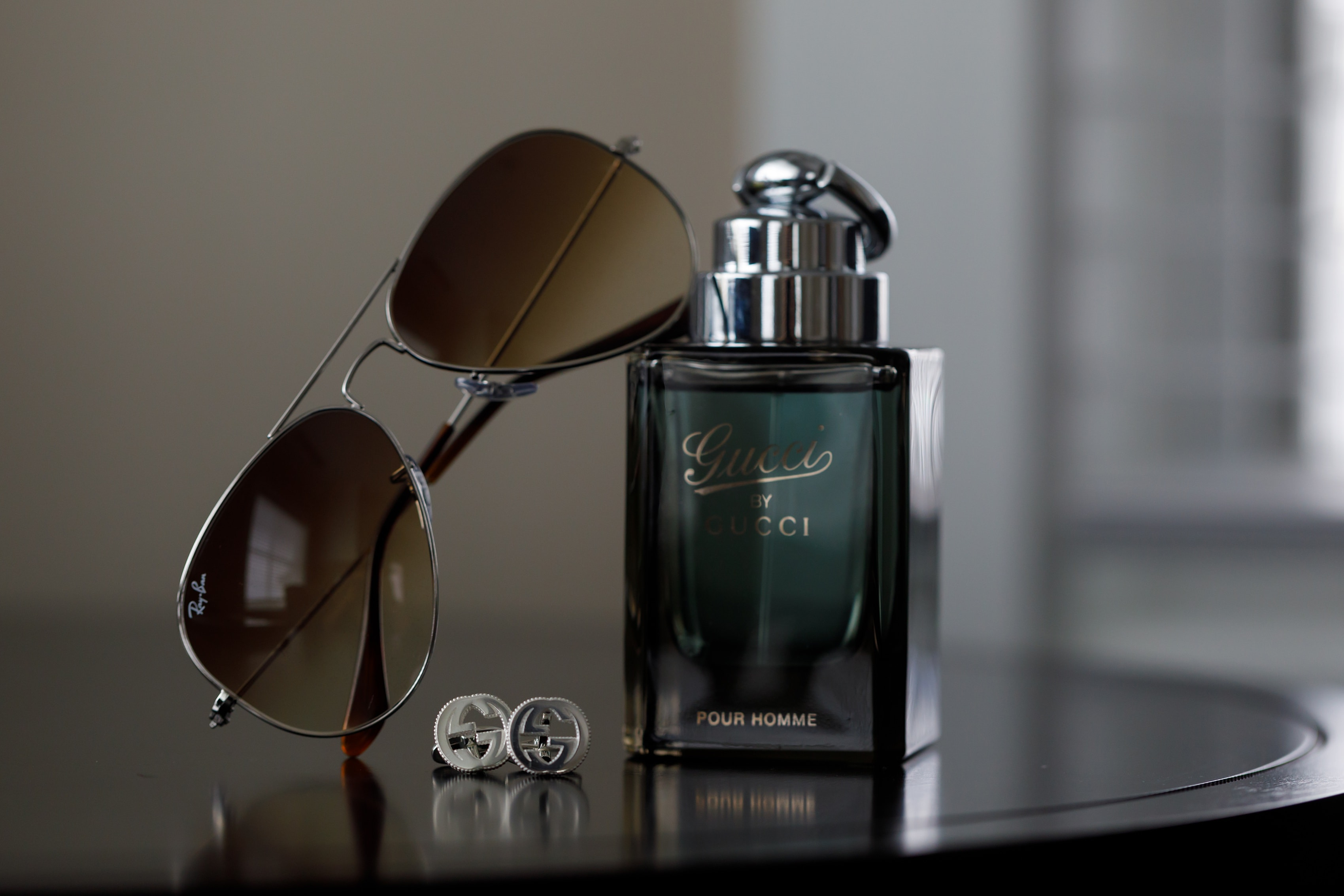 detail of Gucci cologne, cuff links and Ray-Ban sunglasses