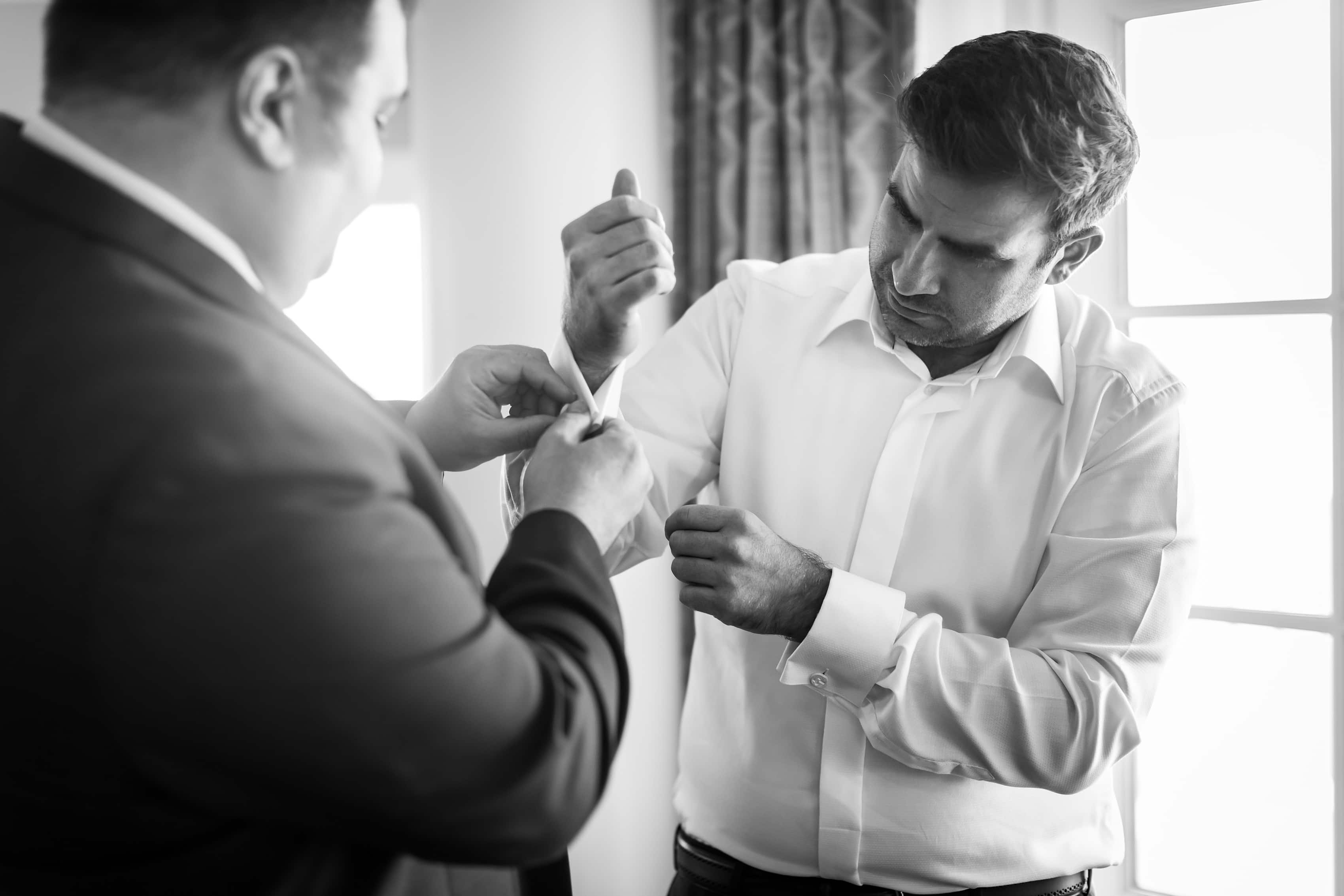 Groom gets ready for his wedding by doing cuff links with groomsmen