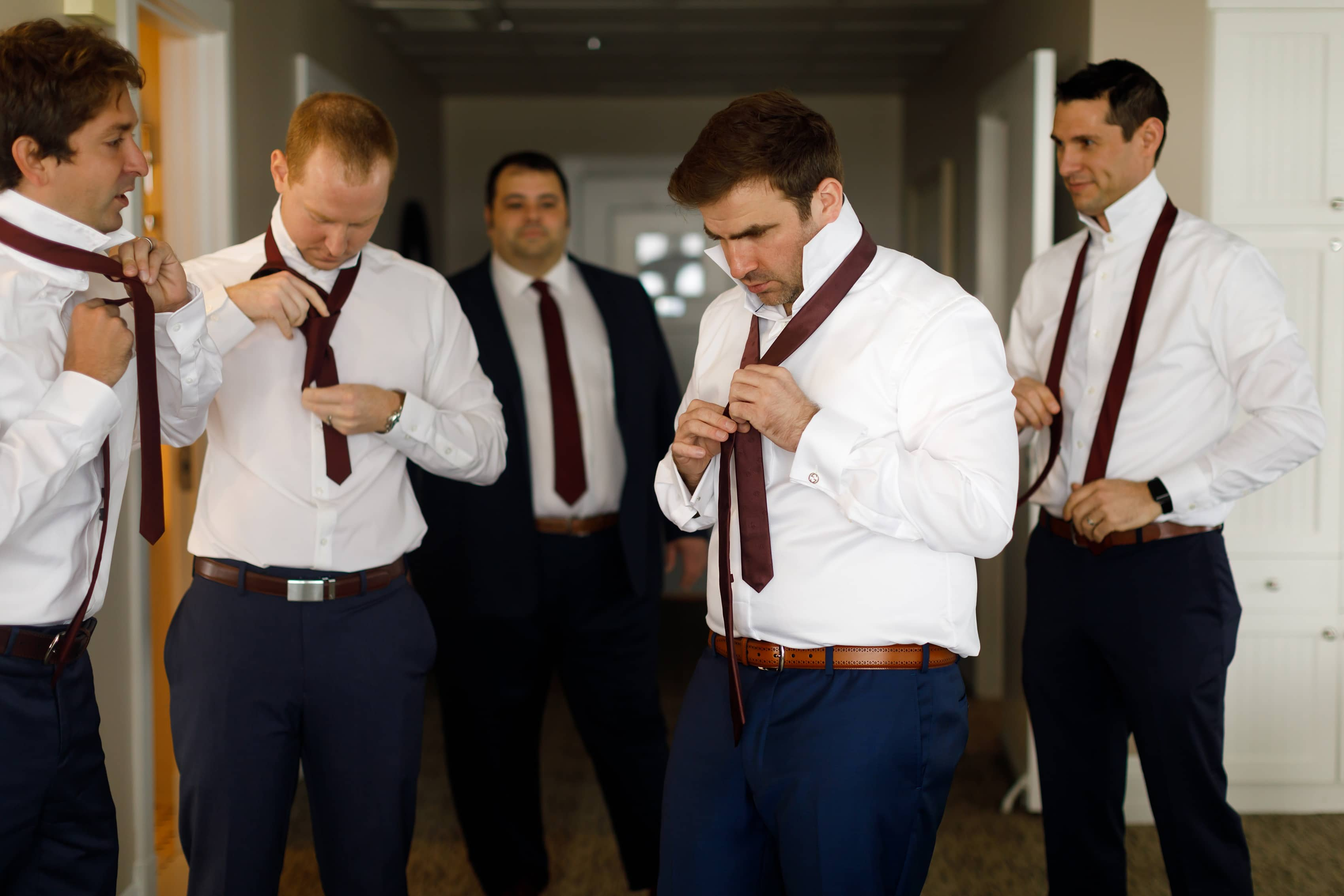 groom and groomsmen put on ties while getting ready for wedding
