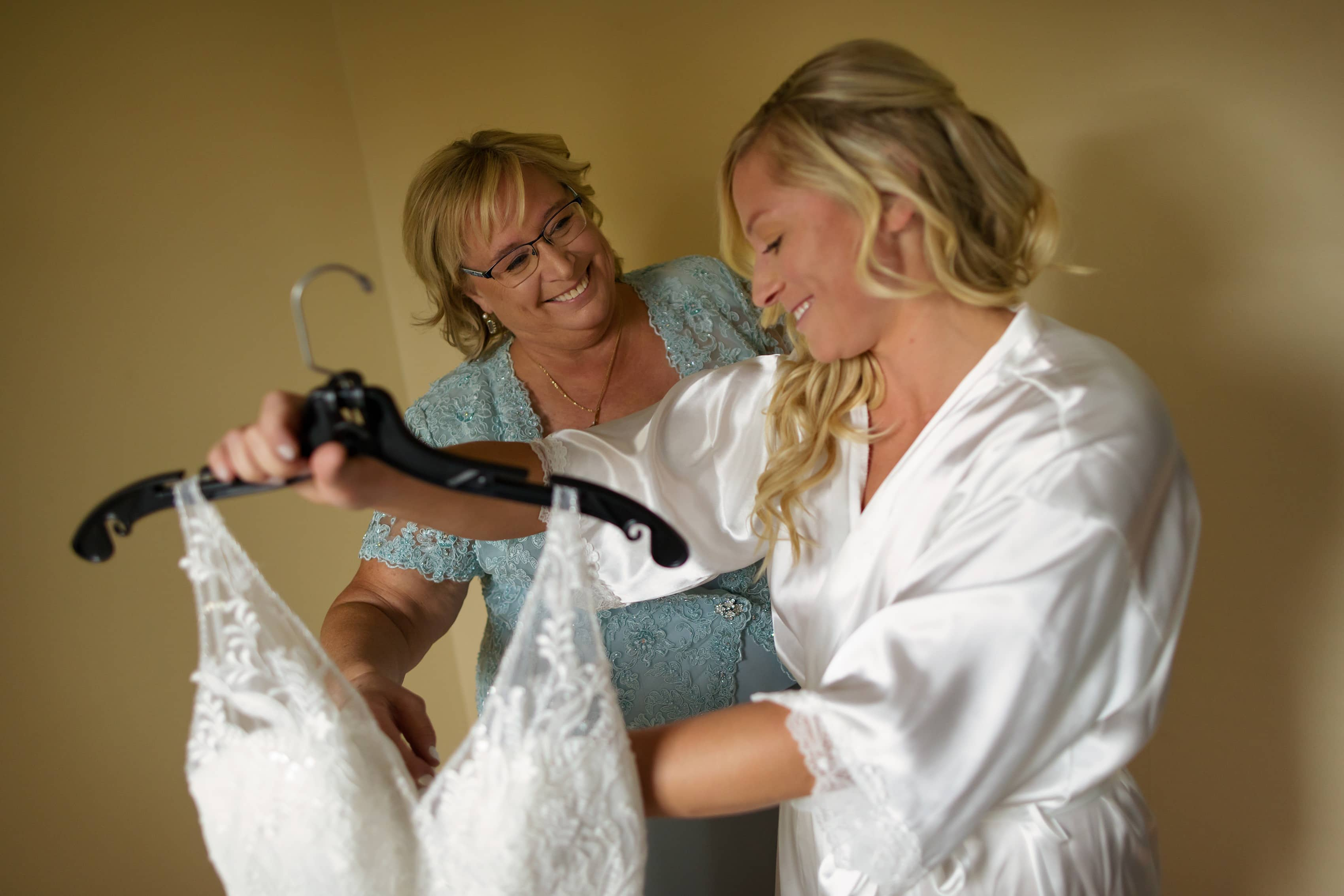 bride and mom smile while getting ready to put on wedding dress