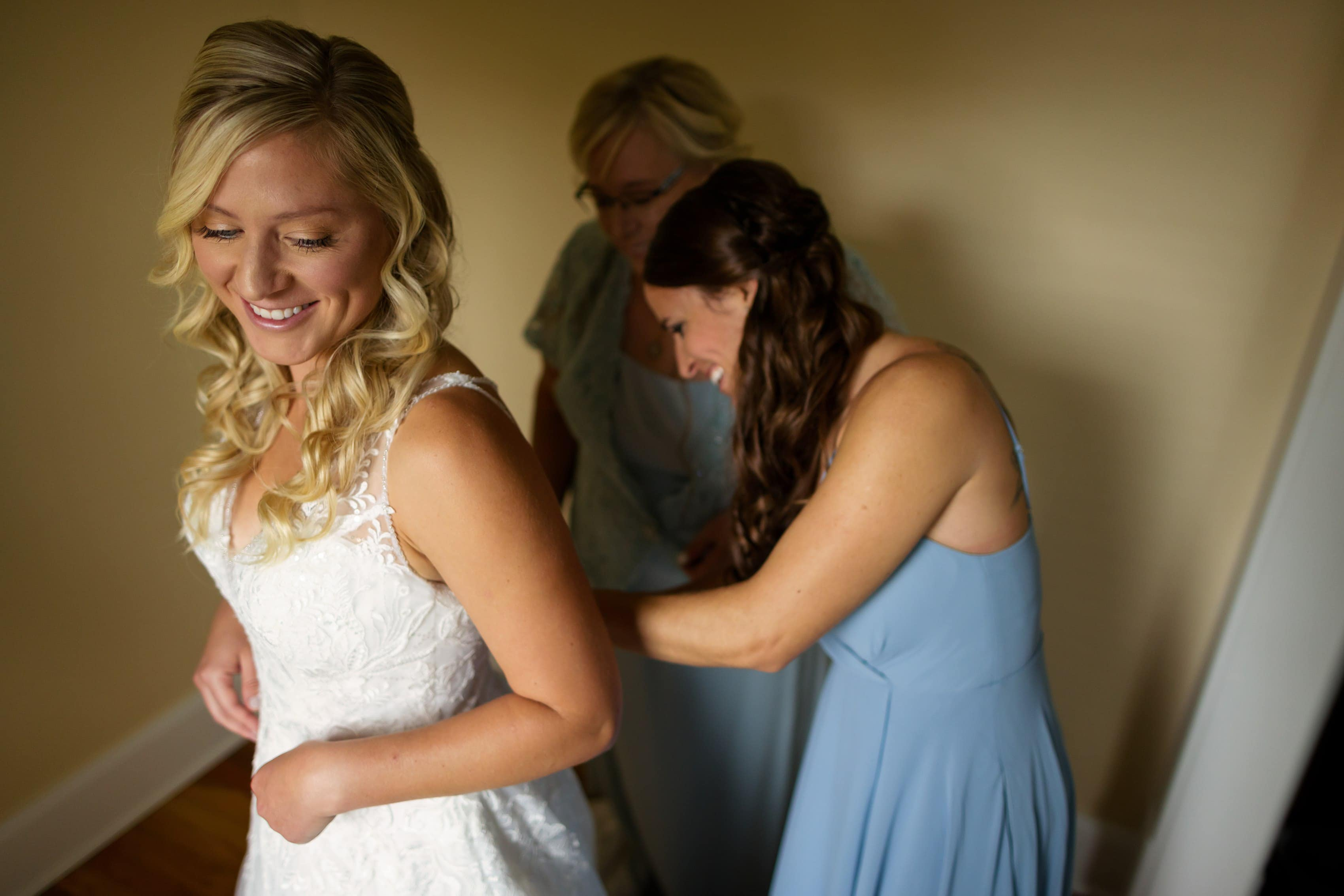 bridesmaid and mother help bride into dress