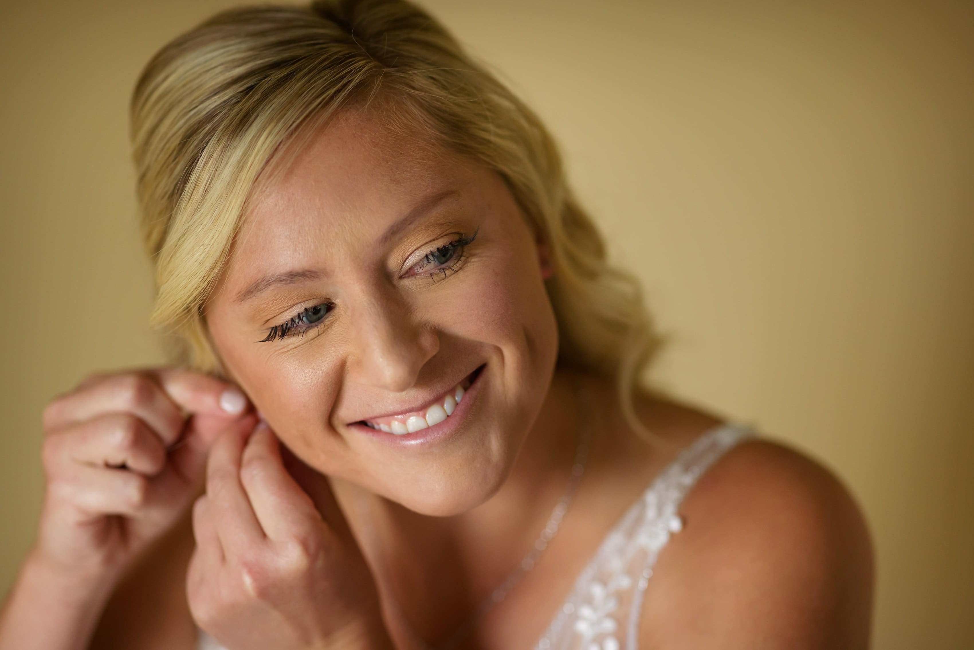 bride smiles while putting earrings in getting ready for wedding