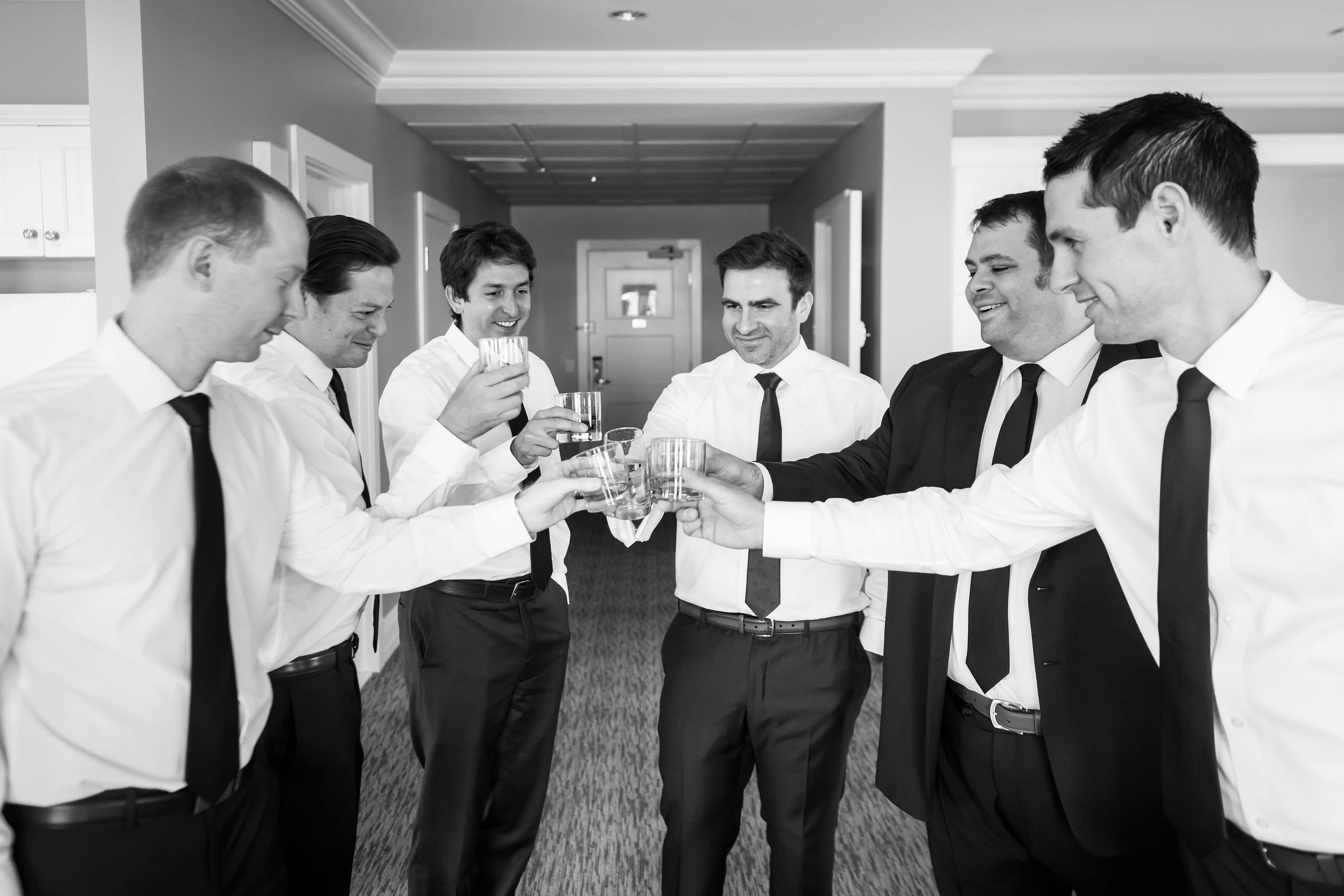 groomsmen raise glasses for toast before wedding