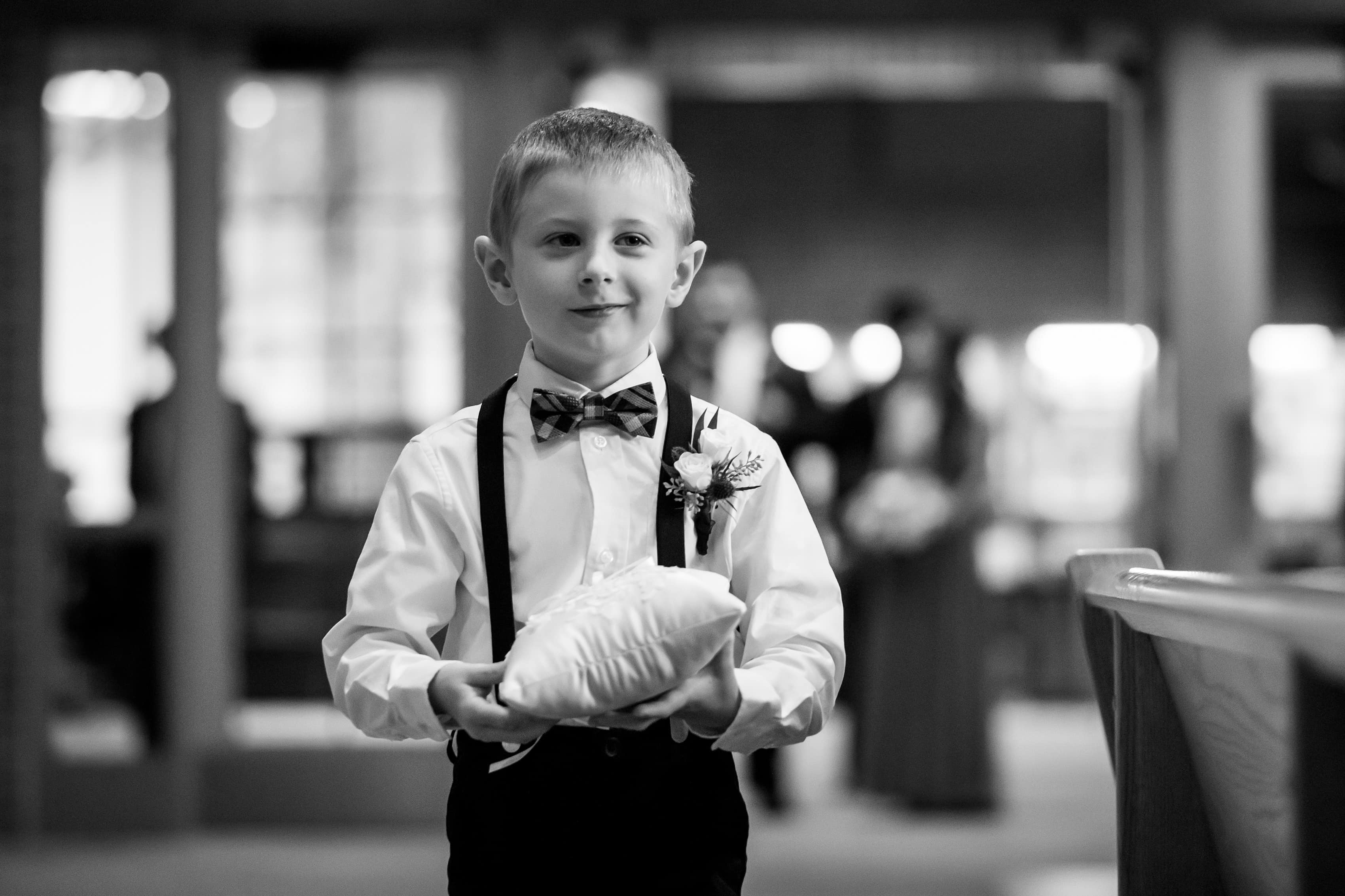 ring bearer walks down the aisle during wedding ceremony