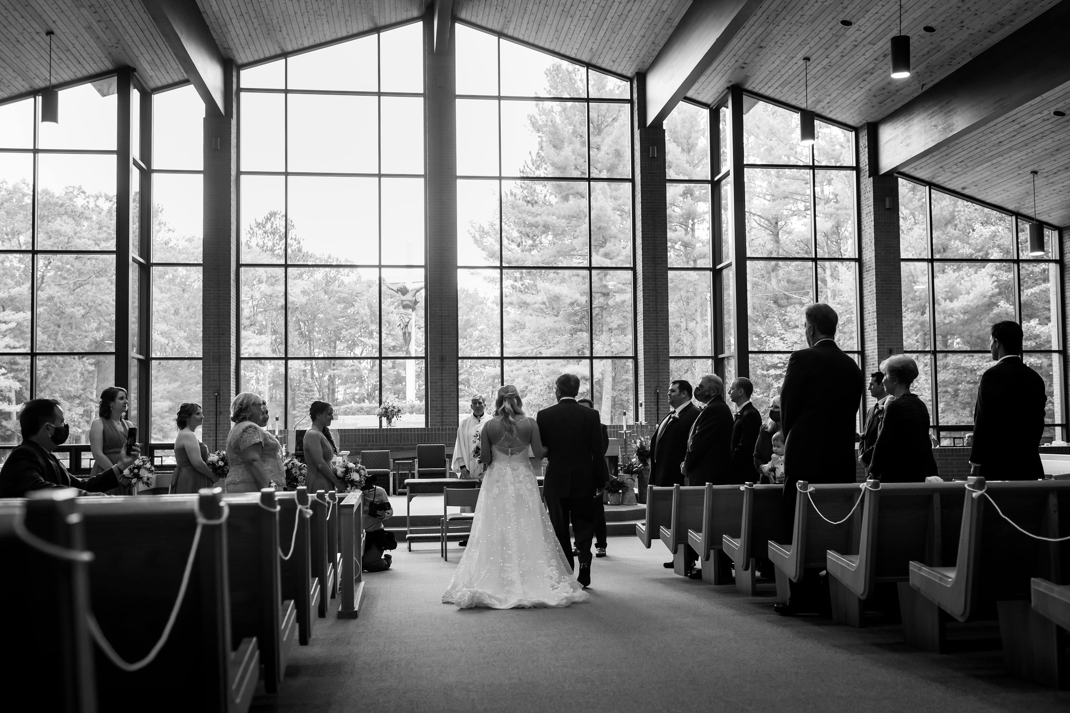 Bride walks down the aisle with her father during wedding ceremony at Cross in the Woods in Indian River, Michigan