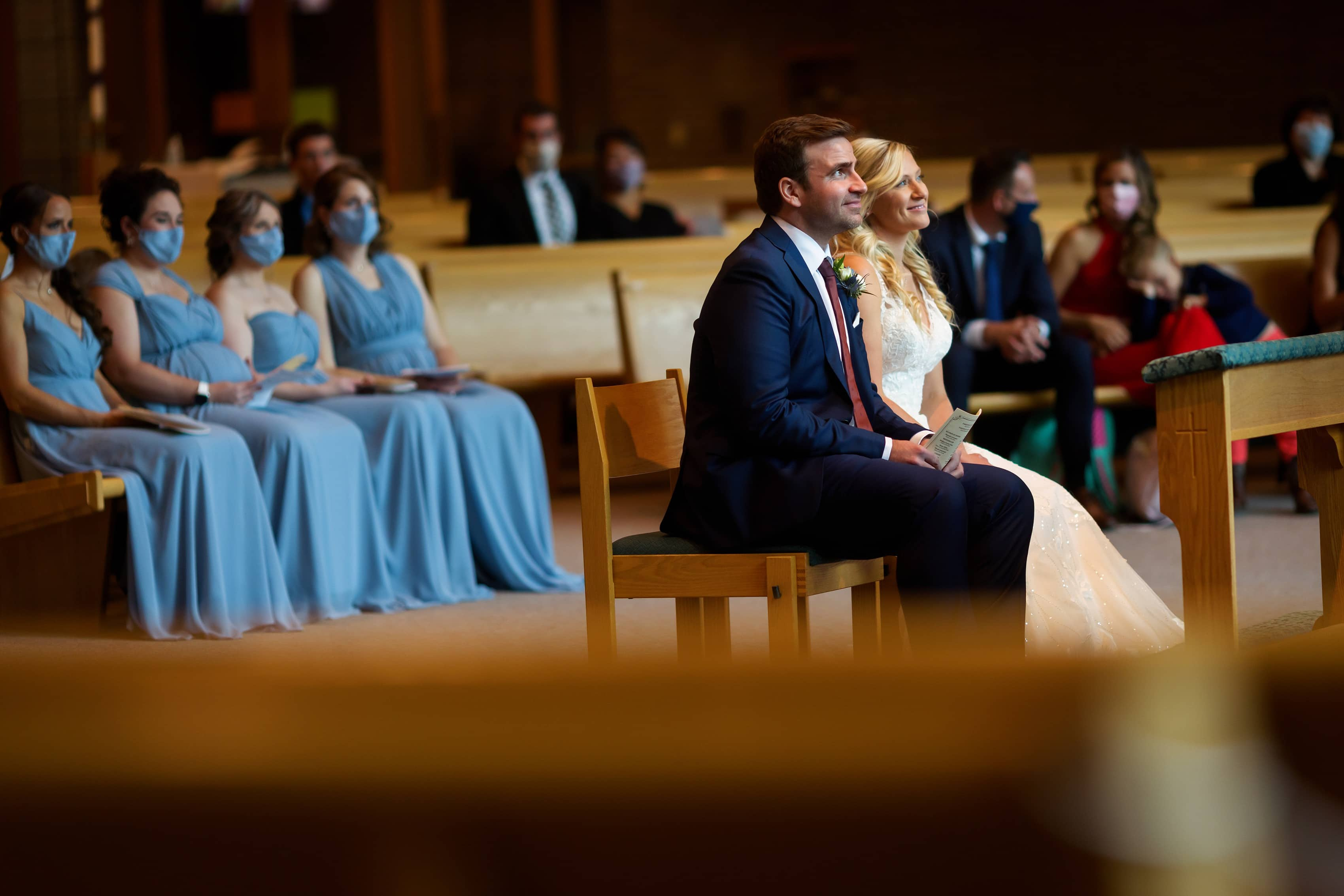 bride and groom smile during wedding ceremony at Cross in the Woods in Indian River, Michigan