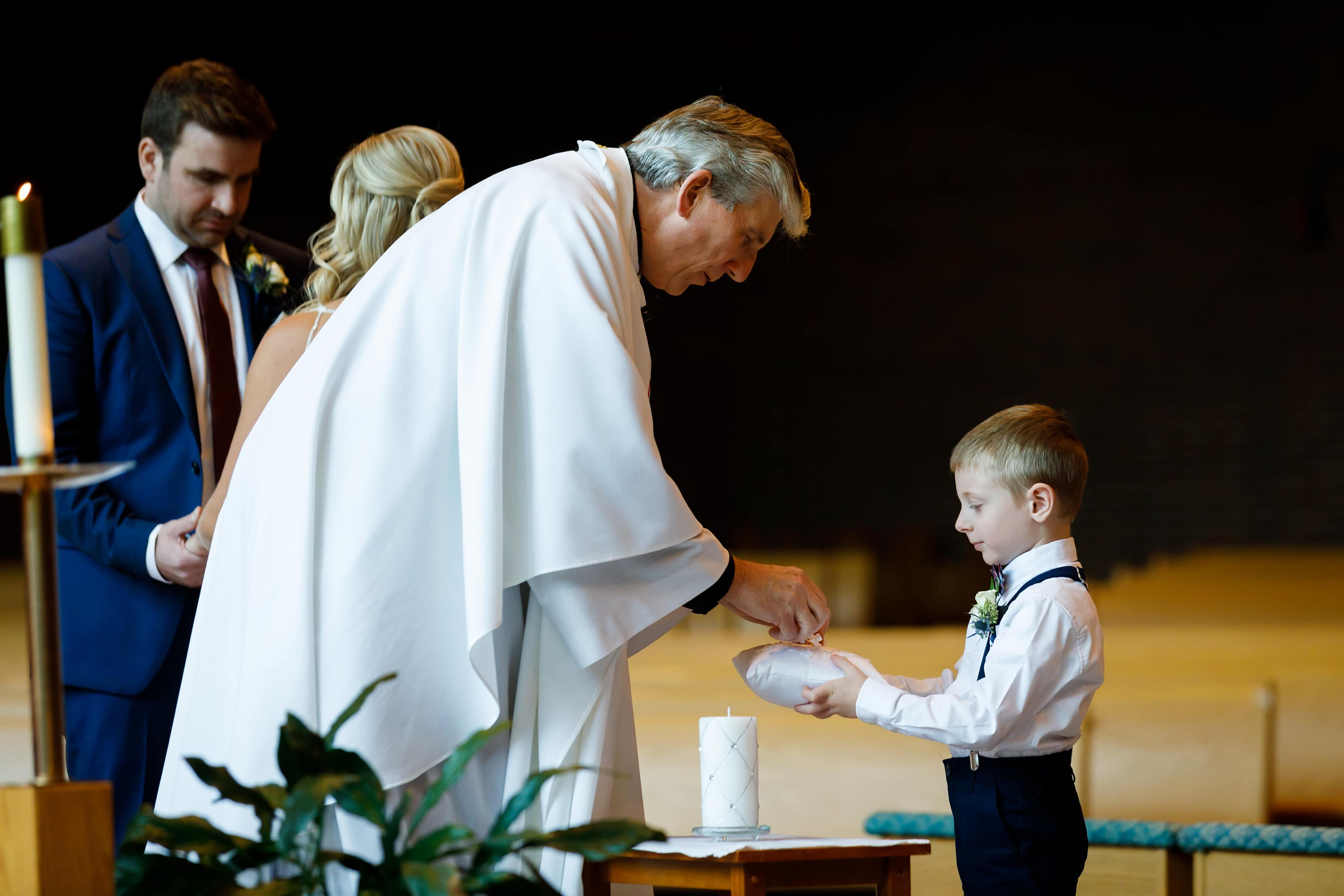 Ring bearer delivers wedding rings during wedding ceremony at Cross in the Woods in Indian River, Michigan