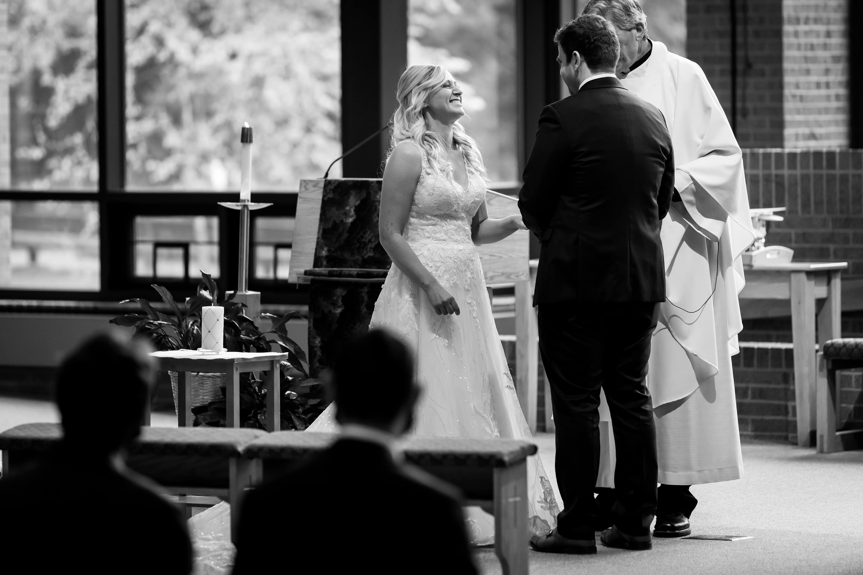 bride and groom laugh while exchanging vows during wedding ceremony at Cross in the Woods in Indian River, Michigan