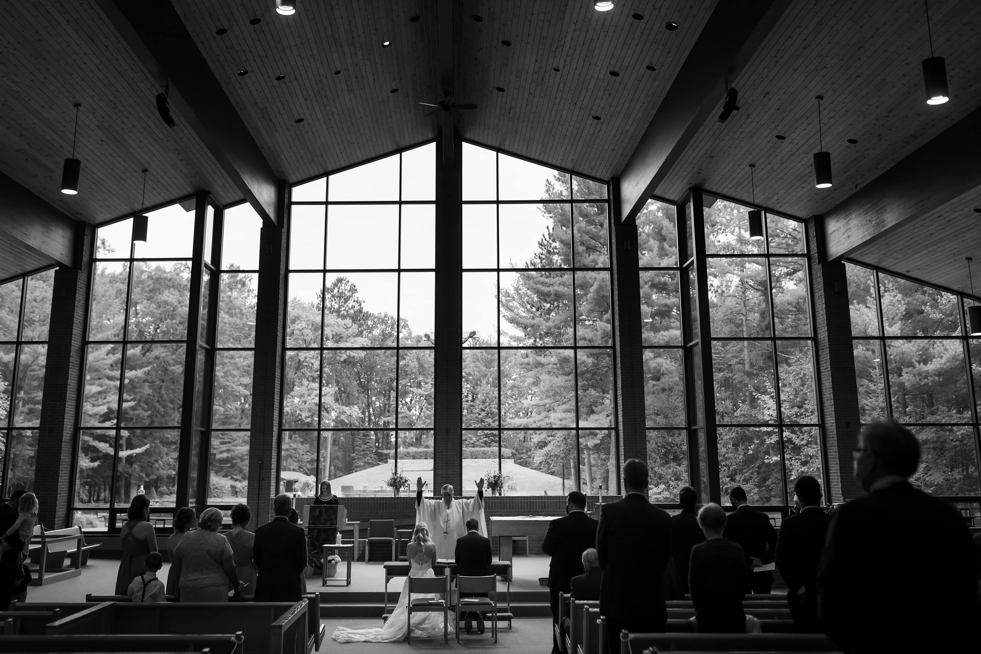 wide angle photo of indoor wedding ceremony at Cross in the Woods in Indian River, Michigan