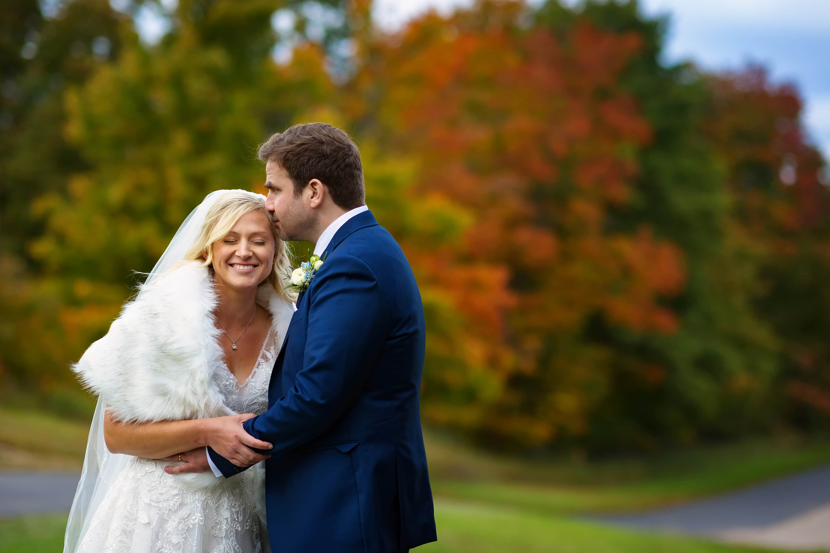 bride and groom pose for wedding portraits at Petoskey Farms with fall colors in the background